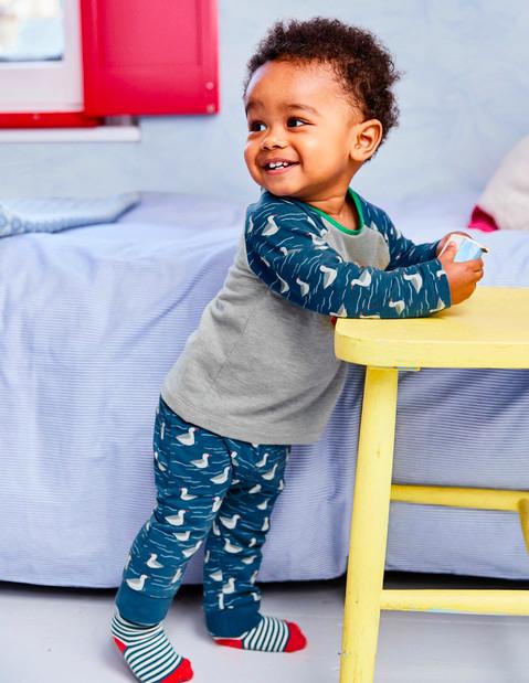 Baby in Boden pyjamas in a nursery with Seascape wallpaper