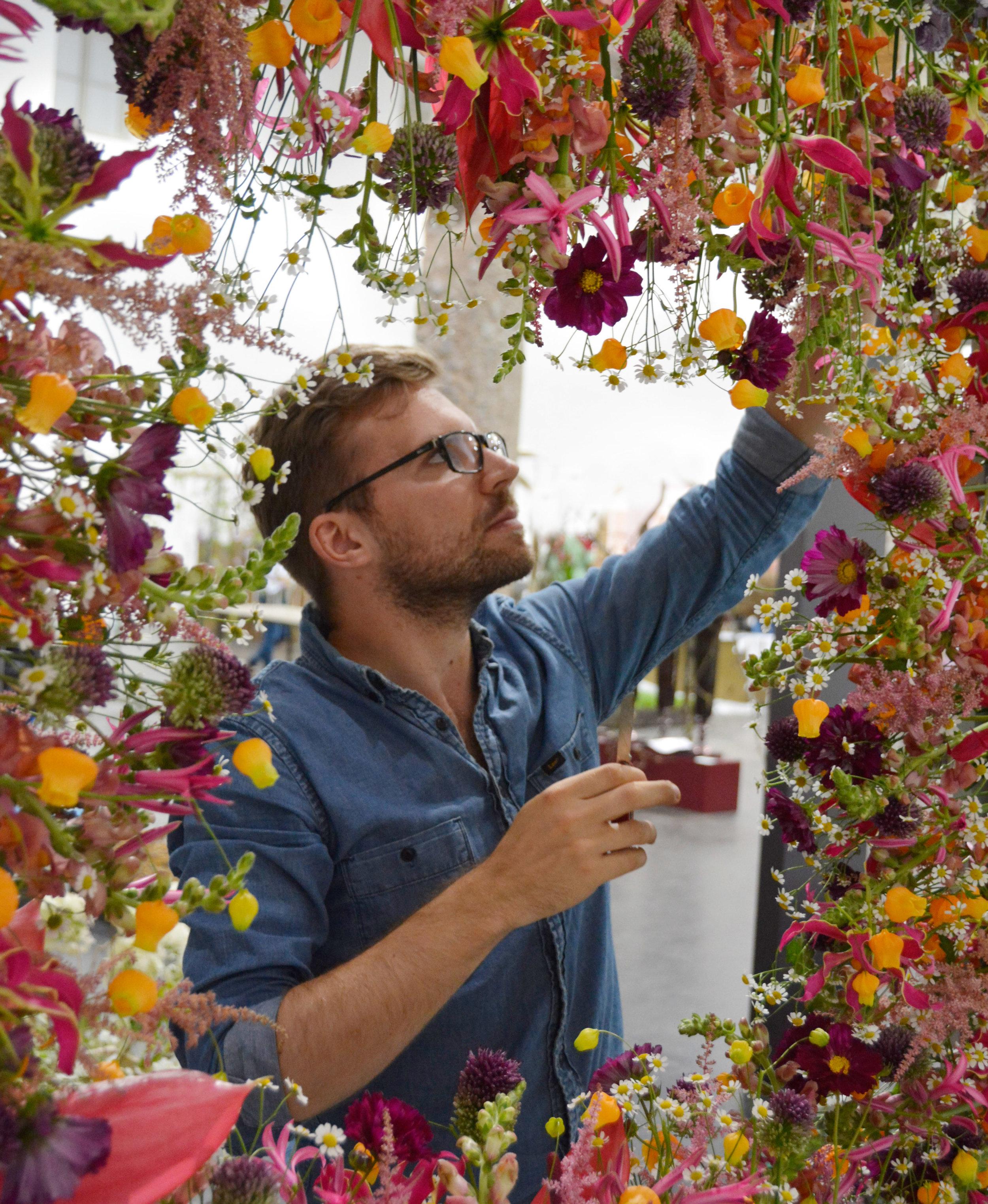 Der Münchner, Benedikt Alberter, der zur Zeit in der Schweiz lebt und arbeitet, schuf einen so eindrücklichen Rahmen aus Blüten, dass er es sich leisten konnte, das Bildinnere offen zu lassen.