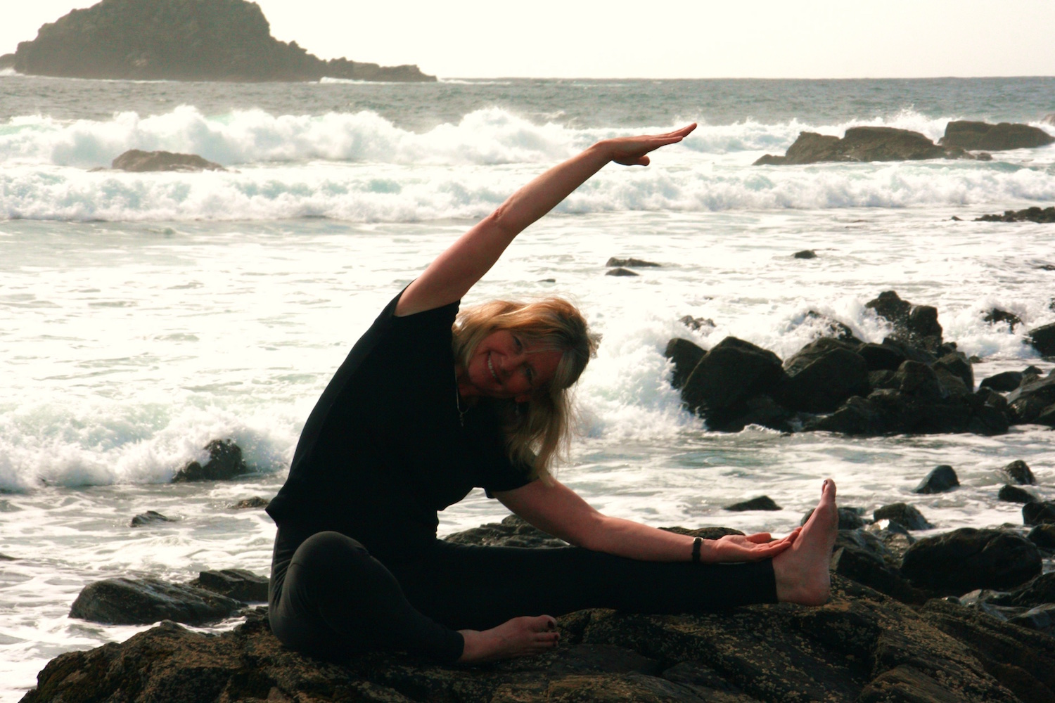 Fiona Moyle practicing yoga on the Cornish coast.