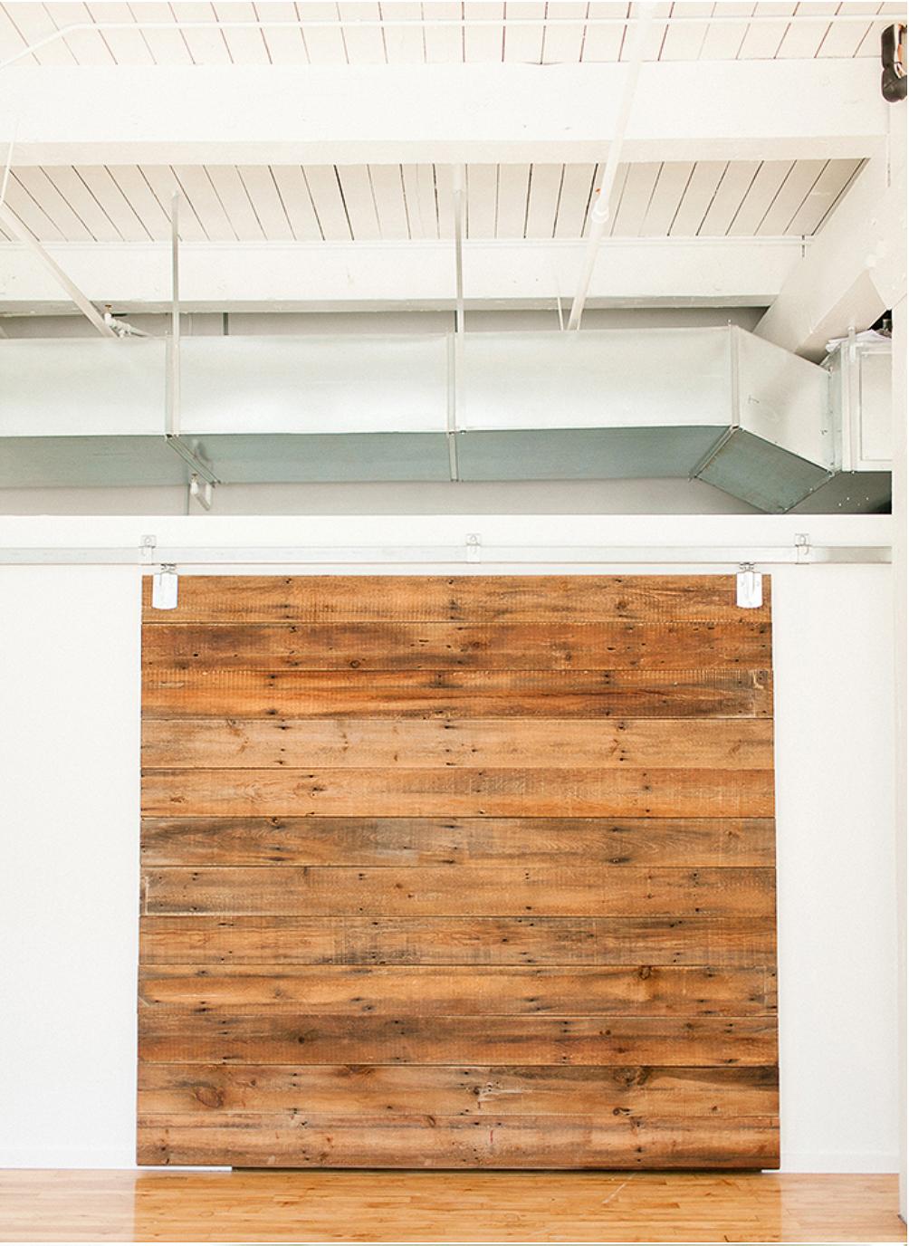 Custom-made sliding barn door reveals a dressing room and storage area.