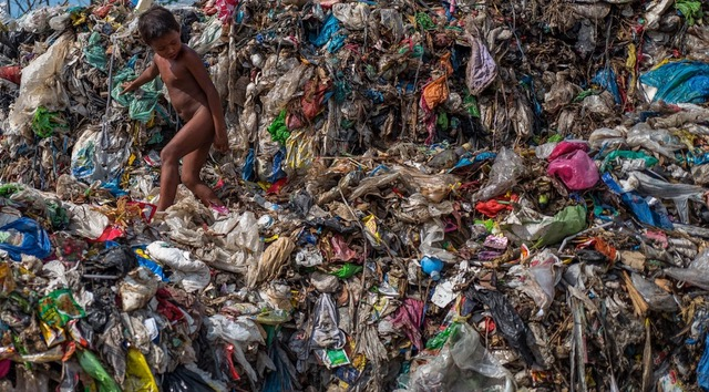DAGUPAN, PHILIPPINES. A YOUNG BOY CLIMBS OVER PLASTIC DEBRIS IN A 50-YEAR-OLD DUMP OVERLOOKING THE OCEAN IN THIS SEASIDE TOWN. MOST OF THE BIODEGRADABLE ITEMS HAVE LONG SINCE ROTTED, LEAVING A MOUNTAIN OF MULTICOLORED PLASTICS THAT FLOAT OUT TO SEA ON THE COASTAL WINDS.