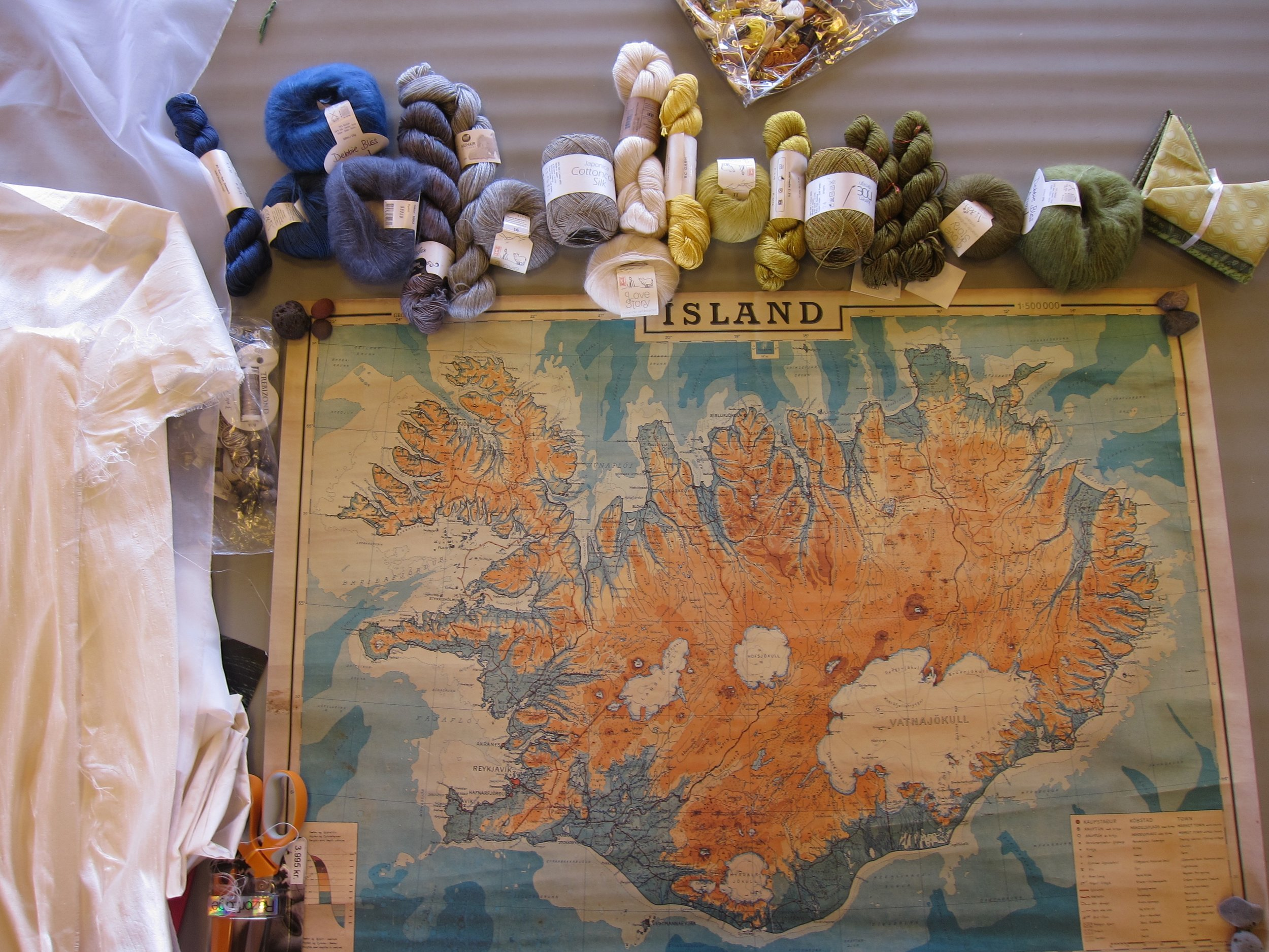 On the left, silks brought from home to be the ground of my map-in-the-making, a modern reprint of a 1963 map of Iceland as starting point, plus a trove of Reykjavík-purchased Icelandic wools and silk yarns for stitching. In this globalized era, it seemed fitting that some yarn was an in-comer, as was I.