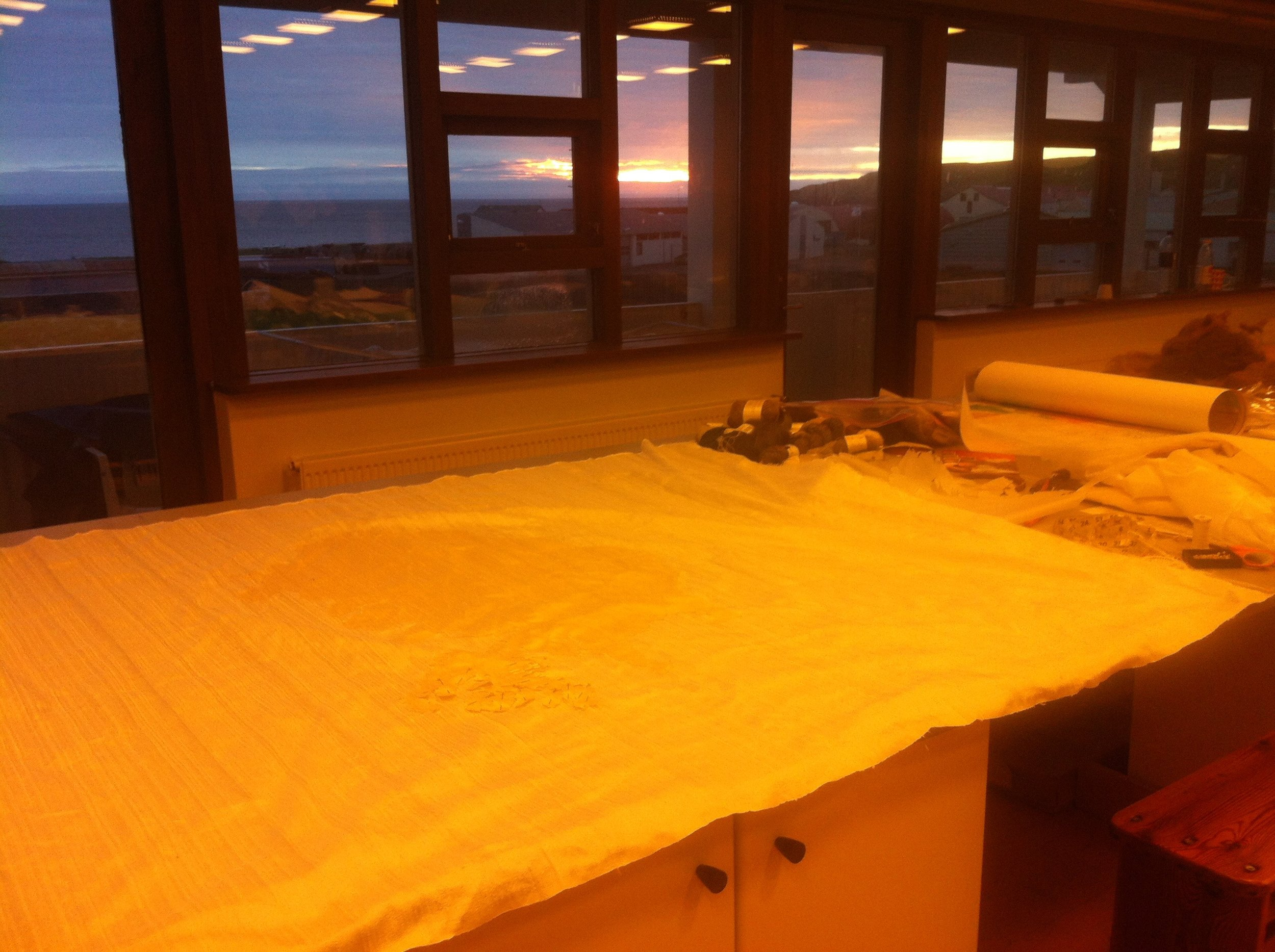 June 2016: Very early morning in the studio at Textílsetur Íslands. The warm tones in the foreground — a photographic oddity created by the tones of the overhead lights. The silk on the table is actually white. Most compelling is the light in the sky, out the windows.