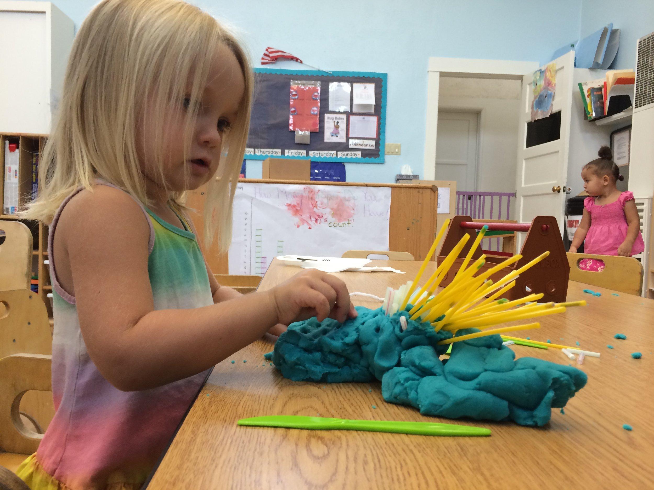 Harper using straws and playdough.jpg