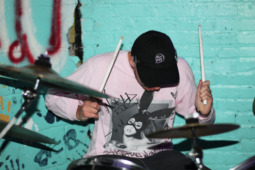 Drummer Paul St. Aubin mid-performance.  Courtesy of Nosebleeds. Photo taken by Sara Soroko.