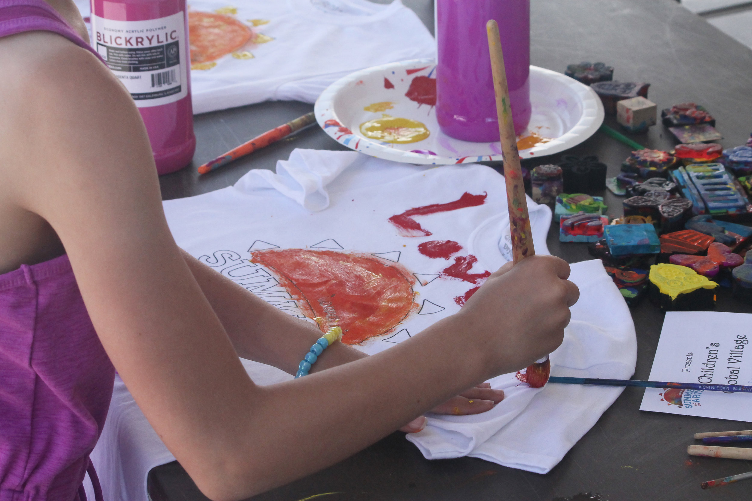 A child paints a Summer of the Arts t-shirt. Photo by Lauren Arzbaecher