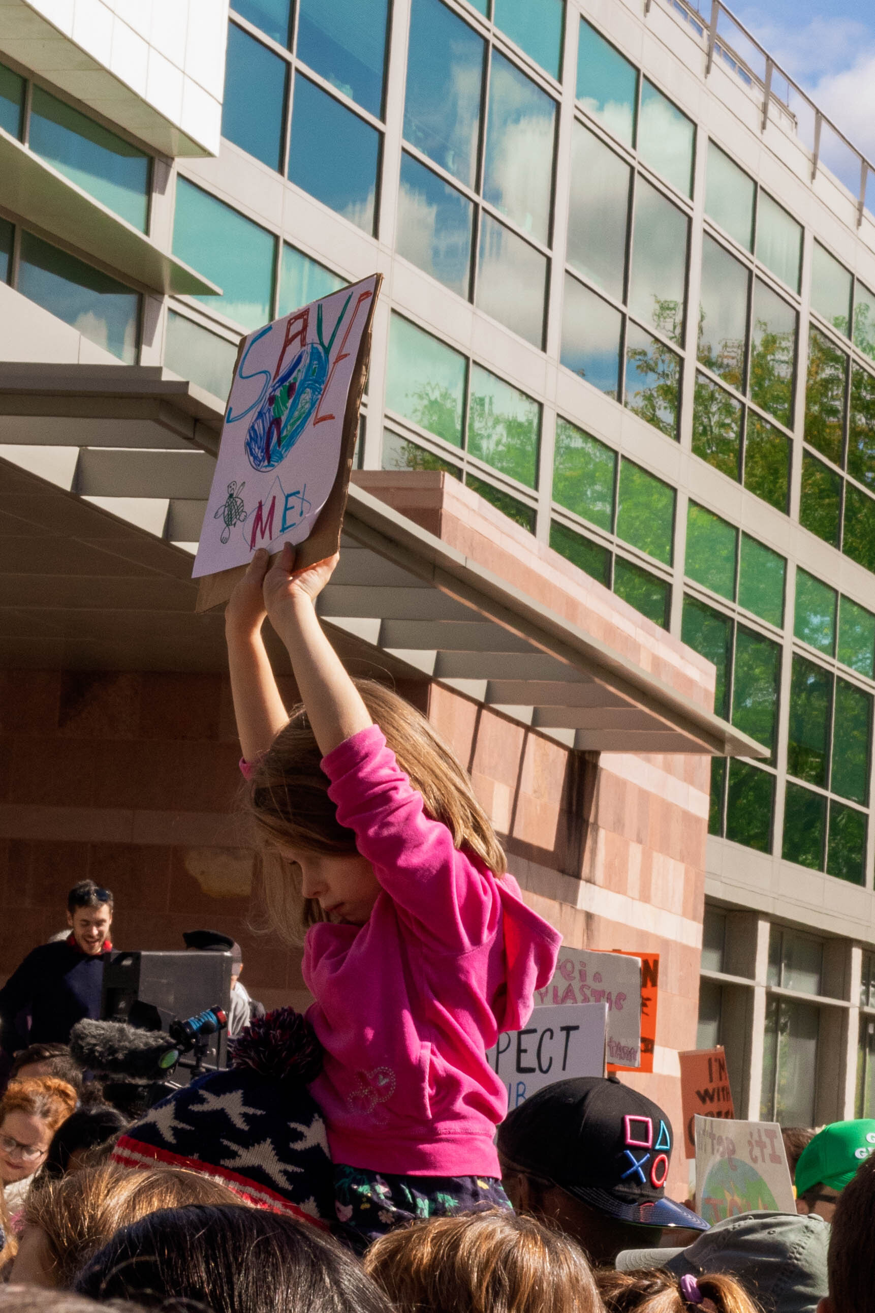 A child holds a hand-drawn sign, demanding the world be saved. Photo by Hayley Anderson