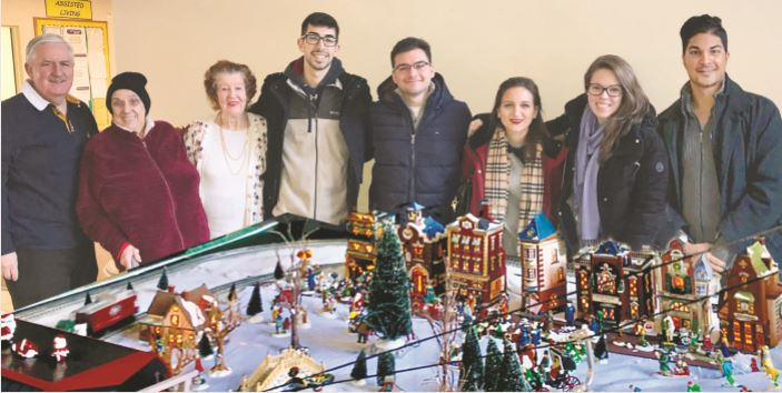 (l to r) This model train show brings joy to local seniors and families and is dedicated to the memory of Michael Cawley Rochford, whose friends also came by to visit. Michael Rochford, Elaine and Mary (Jennings Hall residents), Christian Stellato, Jonathan Coppola, Catherine Ducey, Patrice D'Orozio, Rodney Rubello