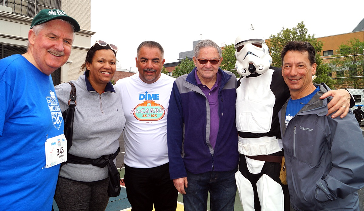 Star Wars Stormtrooper strikes a pose with St. Nicks Alliance leadership. (l to r) Michael Rochford (St. Nicks Alliance Exec. Dir.), Laura James (St. Nicks Alliance Board), Joe Robles (St. Nicks Alliance Board Chair), Frank Citera (Conselyea Block Association VP), and Michael Andrews (St. Nicks Alliance Board)