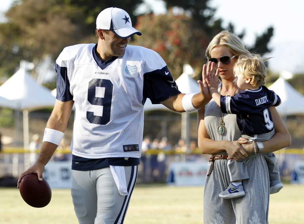Dallas Cowboys quarterback Tony Romo (9) plays with his son Hawkins Romo, 1, as his wife Candice Romo holds Hawkins after the afternoon practice at Dallas Cowboys training camp in Oxnard, California on July 30, 2013. (Vernon Bryant/The Dallas Morning News) 03202014xBRIEFING