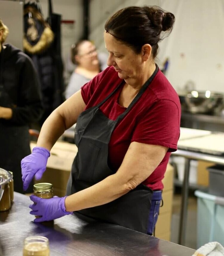 Sandra is on Ground Up's employment training program. Ground Up hires women overcoming homelessness & adversity for 6-12 months. We help them find full-time employment after working in our kitchen and warehouse making nut butter and shipping packages. Here is Sandra in the kitchen making nut butter and lidding jars.