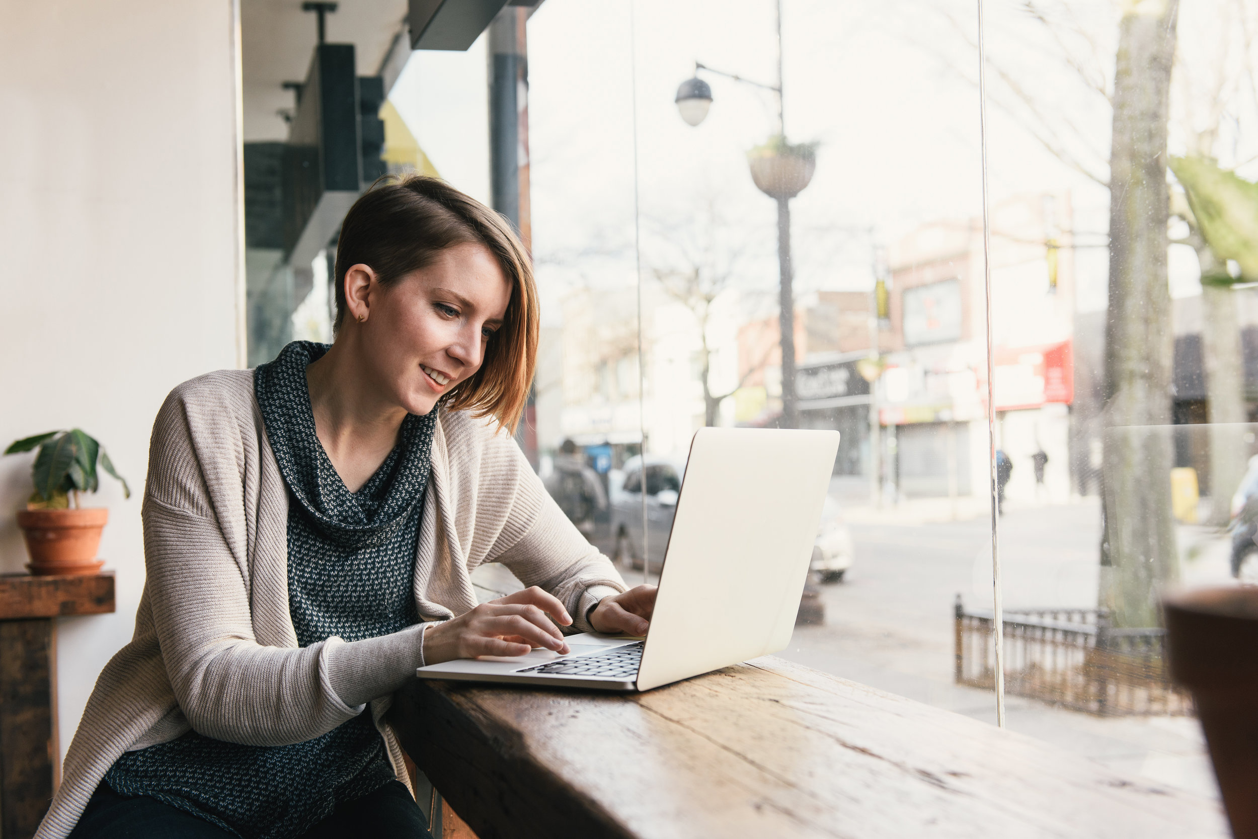 Seller_Seller Center_Female customer sitting in coffee shop window seat typing on laptop.jpg