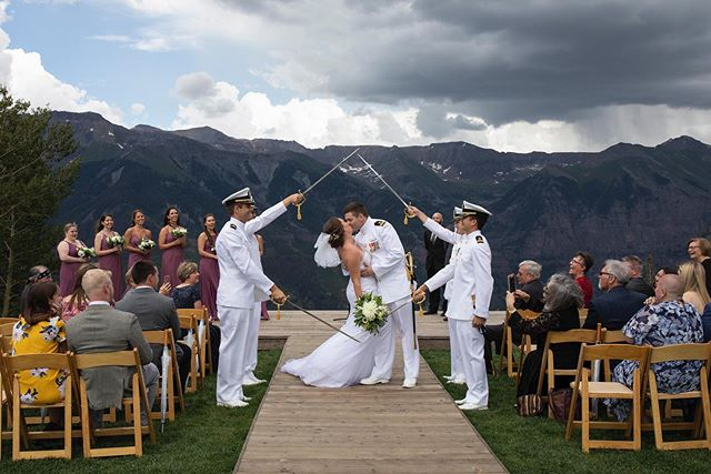 "One of my favorite wedding traditions! The ""arch of sabers"" is a military tradition where the bride and groom pass under an arch of swords in the recessional and after the swords are lifted, the bride gets a gentle swap on the behind from the last soldier who says, ""Welcome to the Navy!"" ⚔️❤️👰🏻 PS - They also cut the cake with the groom's sword - so fun!! . . . . Planner: @telluride_unveiled  Venue: @mountainlodgetride & San Sofia Overlook Video: @joshkingphotography  Floral: @bridalveilfloral  Cake: @wild_rose_cakes  Hair: @lindadoestelluridehair  Makeup: @makeupbyemyb . . . . #outdoorwedding #destinationwedding #mountainwedding #ido #radwedmag #radcouples #loveandwildhearts #belovedstories #weddinginspiration #adventurewedding #coloradoweddingphotographer #tellurideweddingphotographer #coloradowedding #telluridewedding #rockymountainbride #destinationweddingphotographer #militarywedding #archofsabers #archofswords #weddingtraditions #picturesque #telluride #telluridecolorado"