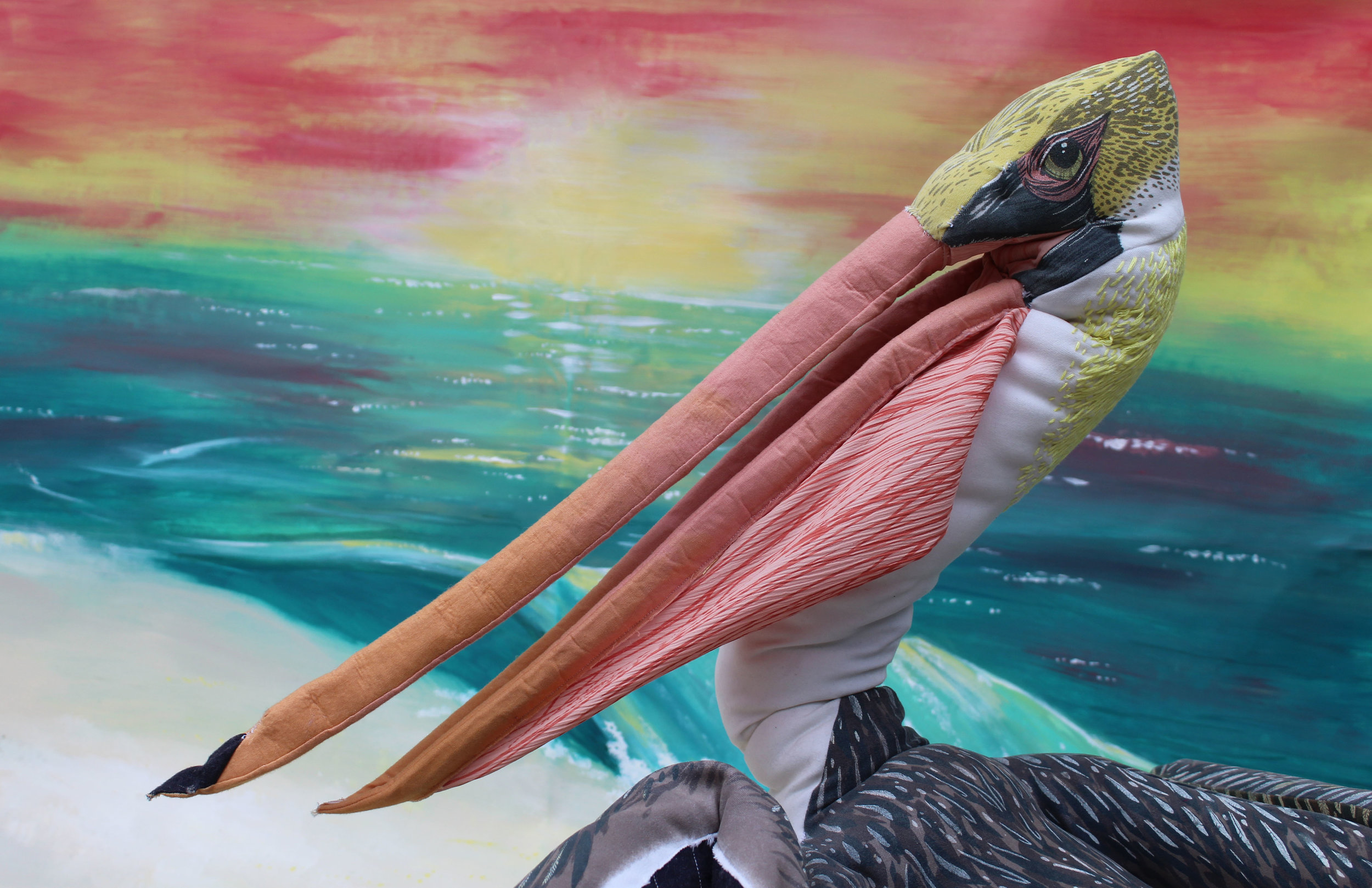The brown pelican is a success story, recently removed from the endangered species list after laws were passed to limit the use ofthe chemical pesticide DDT. Pelican sculpture is life-sized, 3' long with a 6' wingspan, face and back details are screenprinted, neck is hand embroidered,