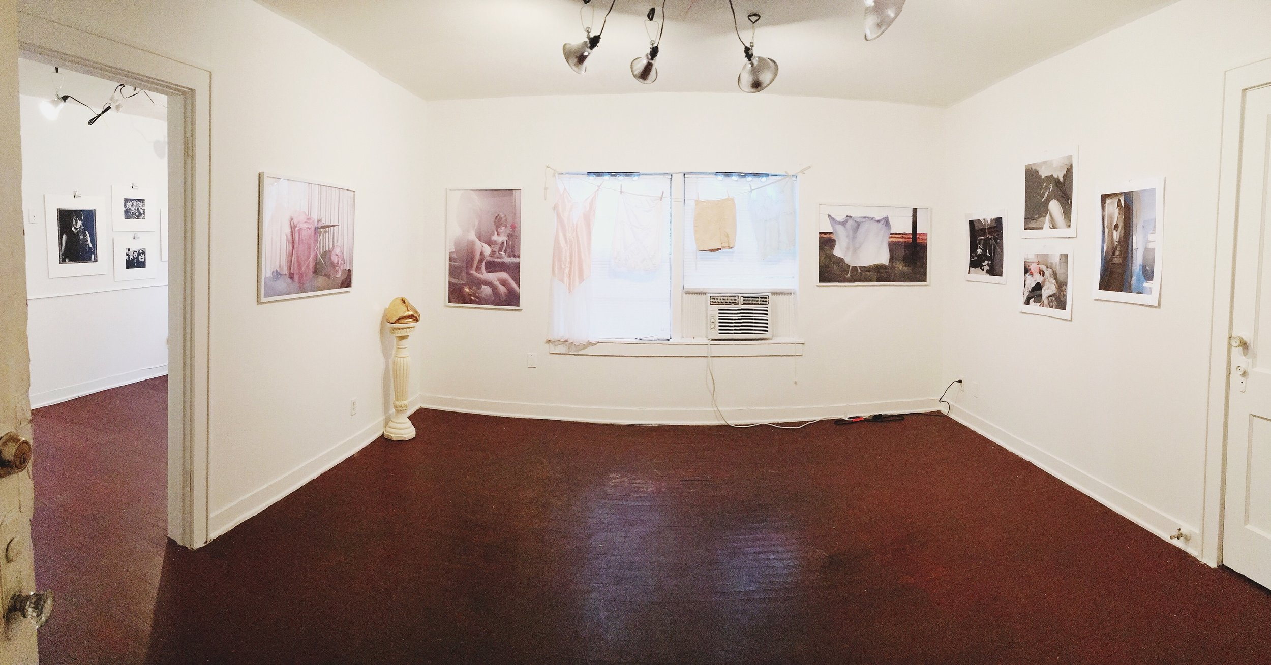 Installation photo from FLATS Presents, Perceptions: Women. A room with white walls has photographs taken by women of women. A window a/c is in the window next to a gold and white sculpture.