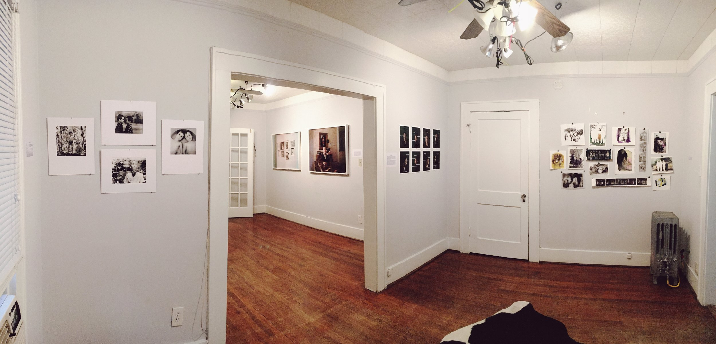 Installation image from FLATS Presents, Fam. Looking through a doorway of a home with photographs in a gallery arrangement on white walls. Artists Clifton Barker, Emilee Cooney, Brenda Edith Franco, Michael O'Brien, Meredith Richey, and Jamie Robertson.