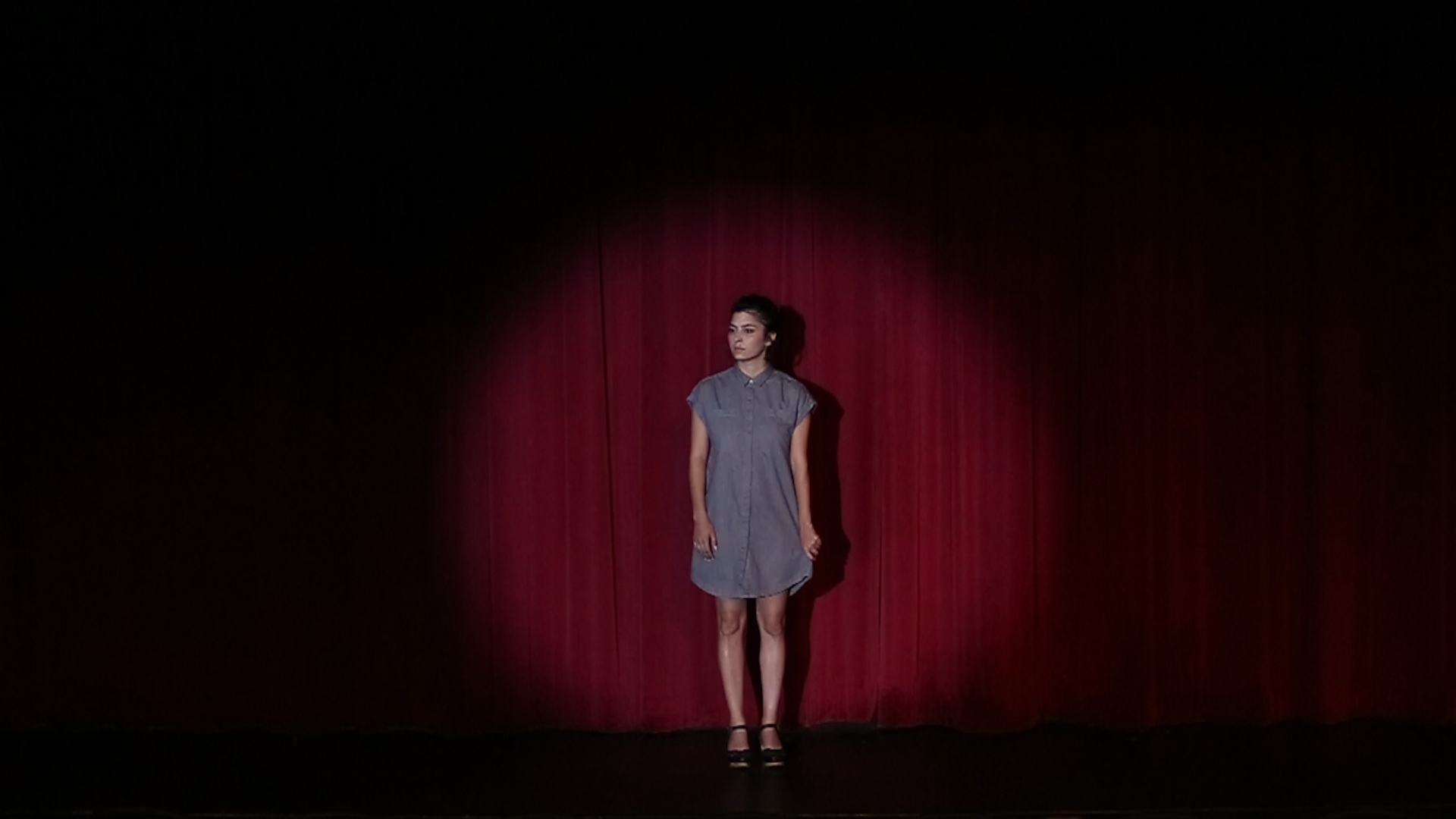 Video still by Houston, TX based Emily Peacock, courtesy of the artist. A person stands on a stage with a red curtain behind them with a spotlight on them.