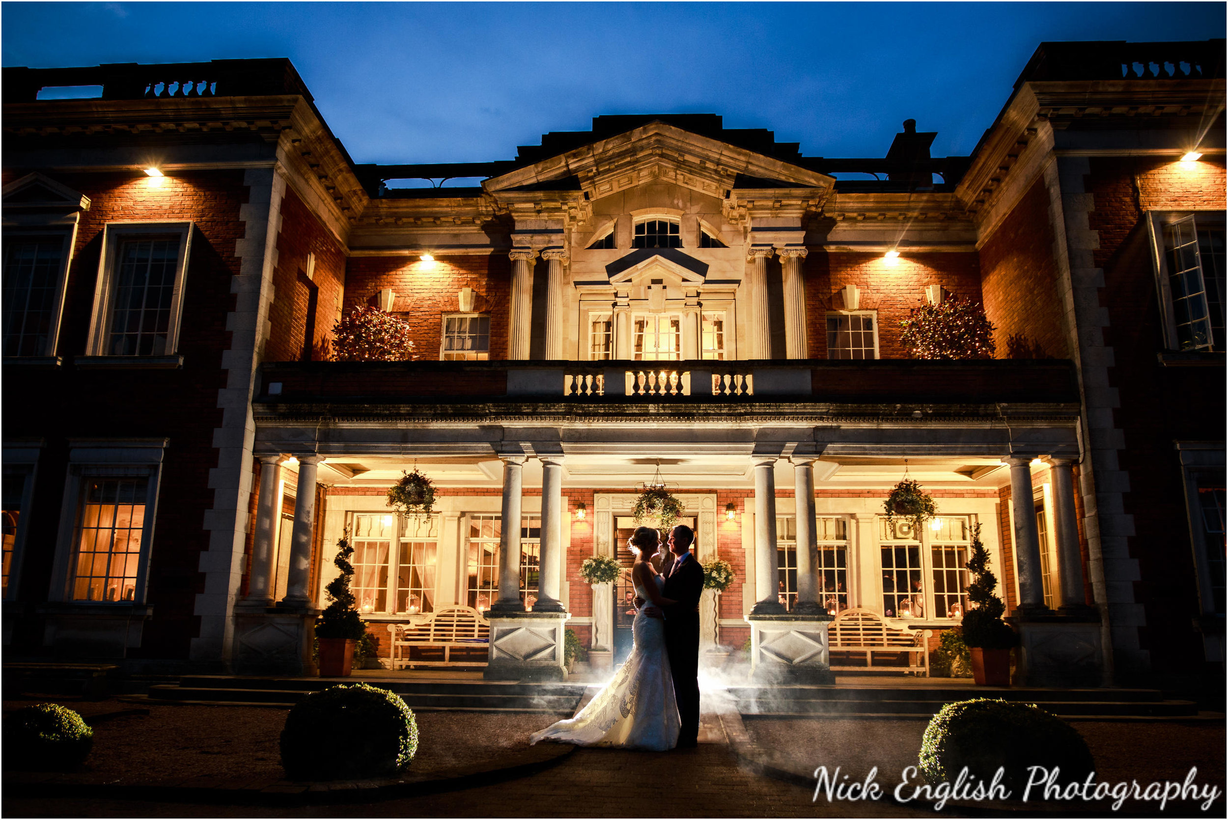 Night shot of bride and groom outside Eaves Hall
