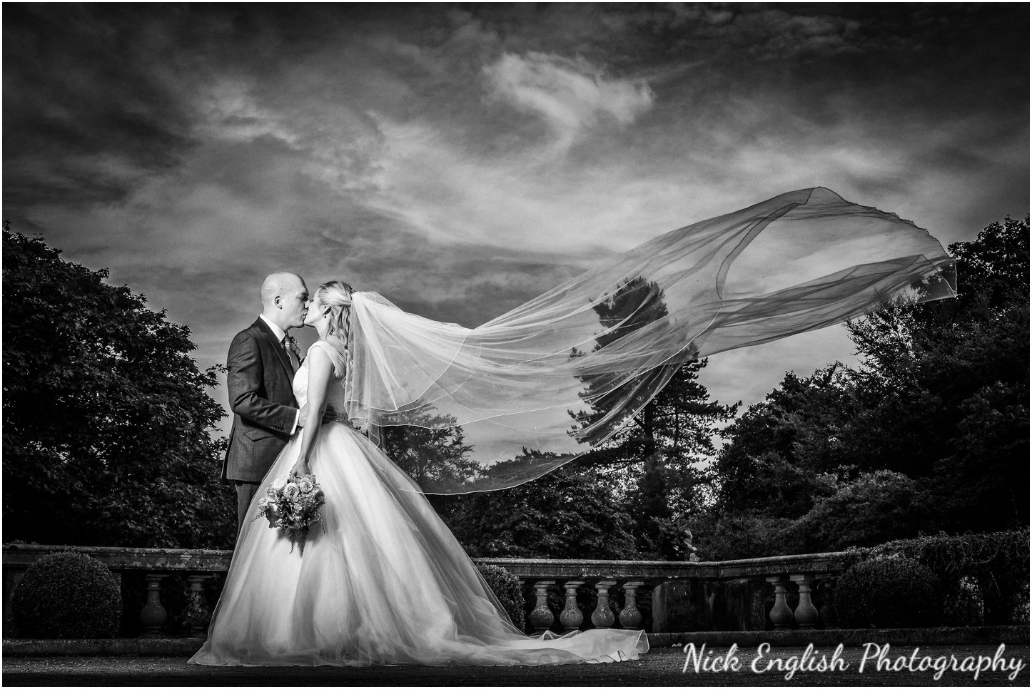 Bride and Groom with wind blowing veil Eaves Hall