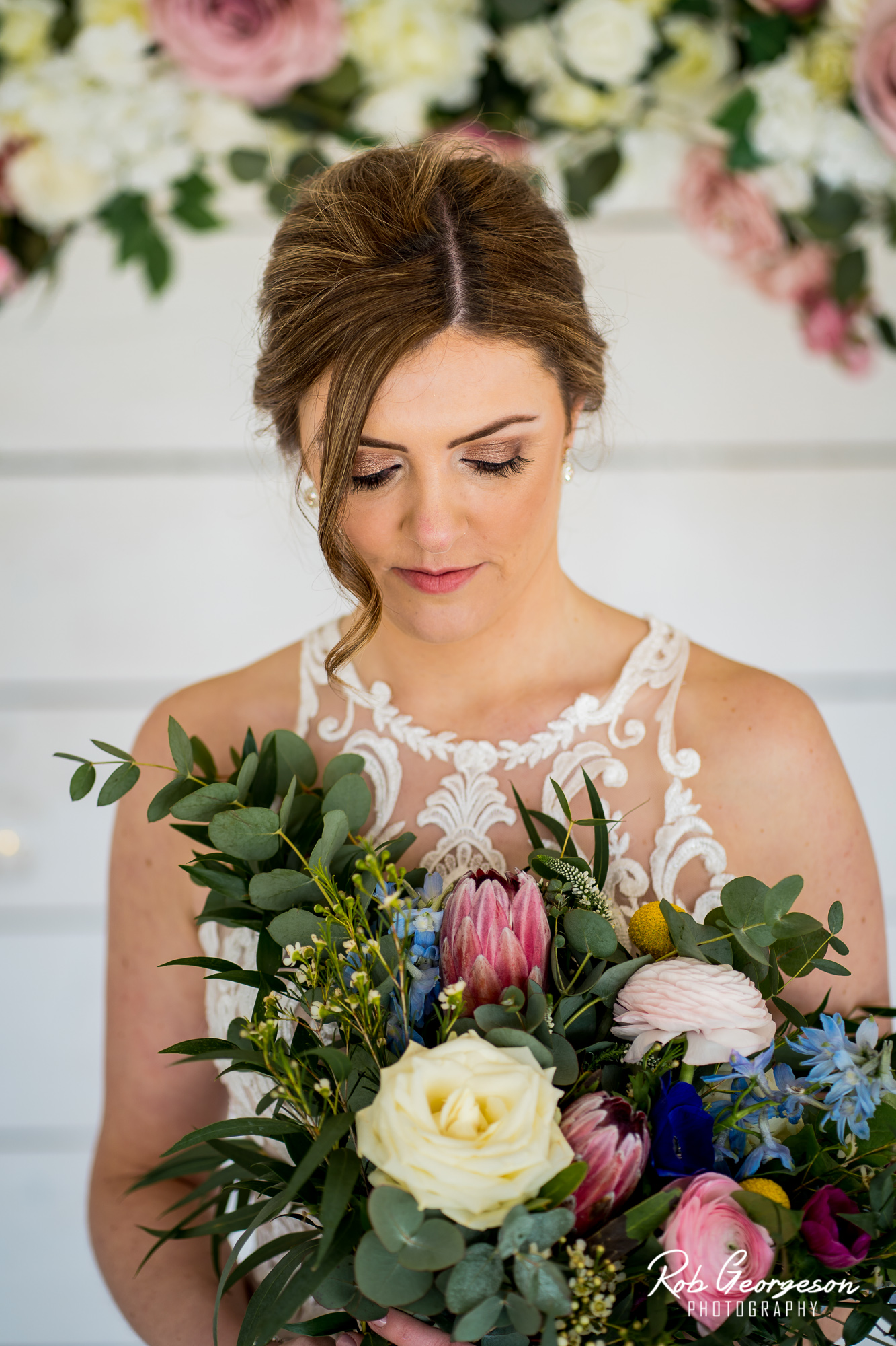bashall barn bride looking at her flower bouquet