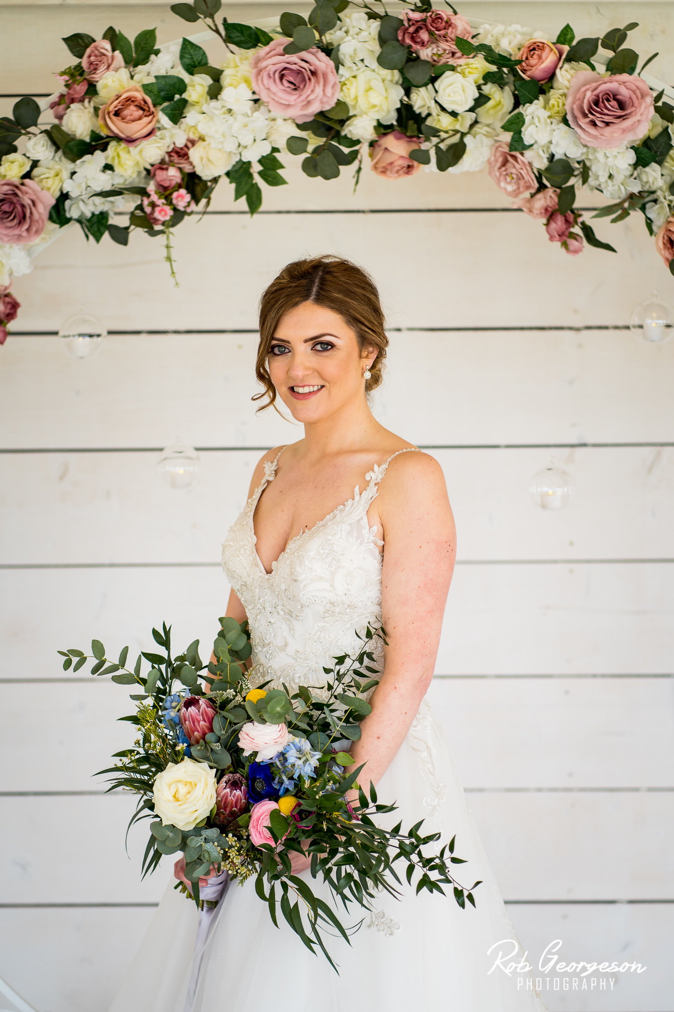 wedding at Bashall barn with a flower wall and bride