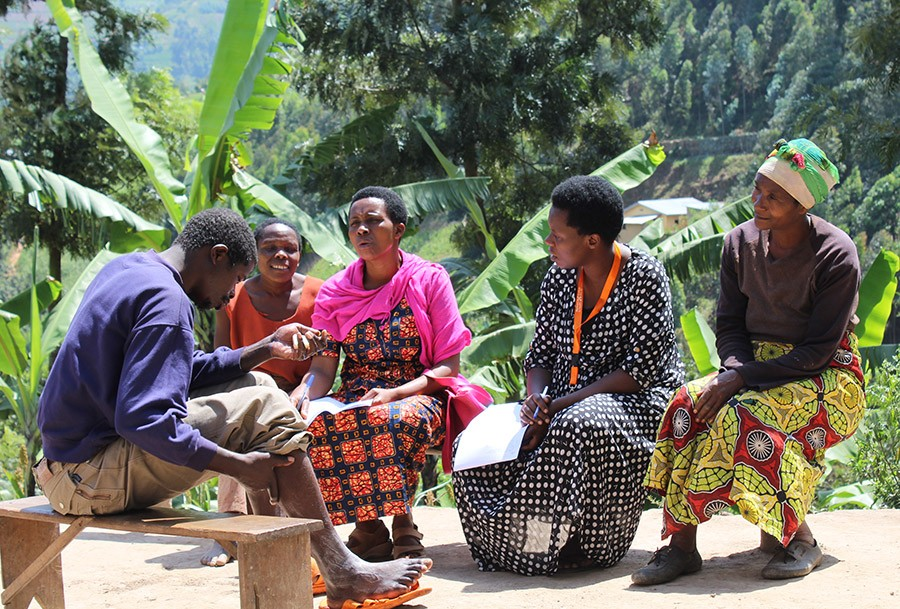 Photos by Bob Muhumuza / Partners In Health Hategekimana Bashar (left), members of his family, and Mental Health Social and Community Support Coordinator Sifa Dorcas (second from right) chat outside Bashar's home in Rwanda in July. Bashar is one of 1,200 Rwandans being treated by PIH's pioneering mental health team.