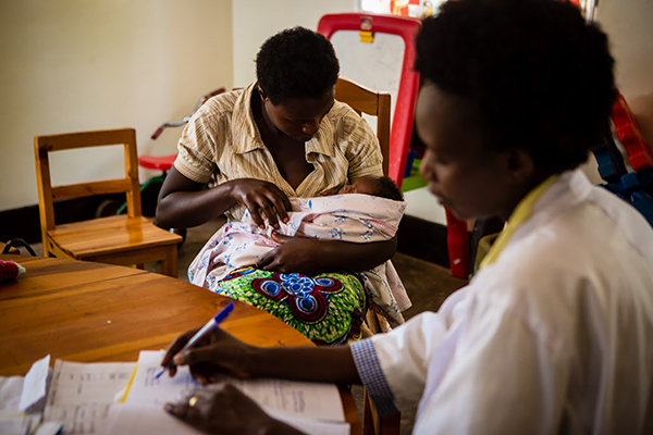 During a weekly Pediatric Development Clinic at Rwinkwavu District Hospital, social worker Alphonsine Umuteri checks in with patient and schedules a home visit.