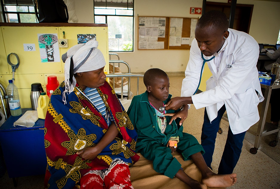 Dr. Cyprien Shyirambere examines 6-year-old pediatric oncology patient Frank Mugisha, whose name has been changed, for privacy, at the Butaro Cancer Center of Excellence in rural northern Rwanda. Medical staff at the PIH-supported facility have treated several thousand patients, young and old, since it opened in 2012. Photo by CecilleCecille Joan Avila