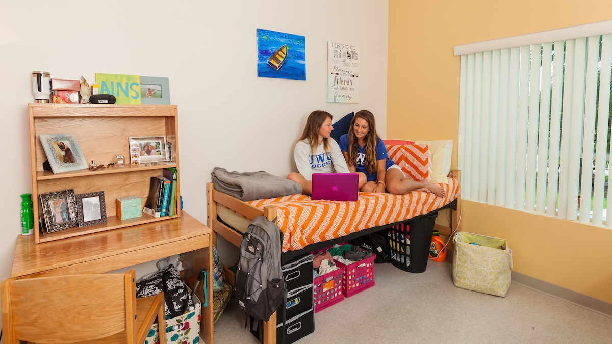 JWU resident students sit on bed