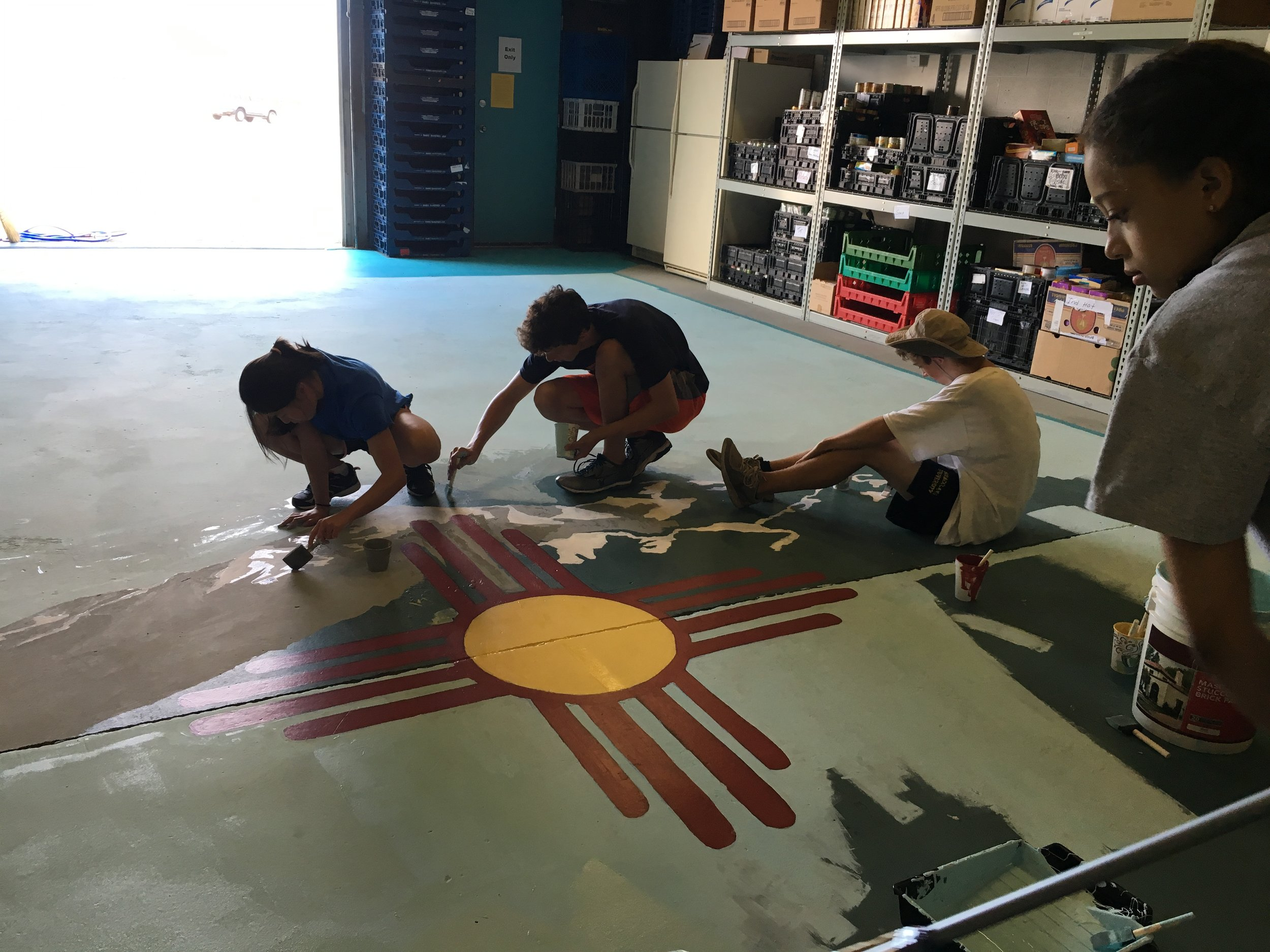 As part of Young Episcopalians in Service Colorado's service trip to Albuquerque, St Barnabas Youth painted the floor of Silver Horizons Senior Food Bank with the emblem of New Mexico and the Sandias Mountains.