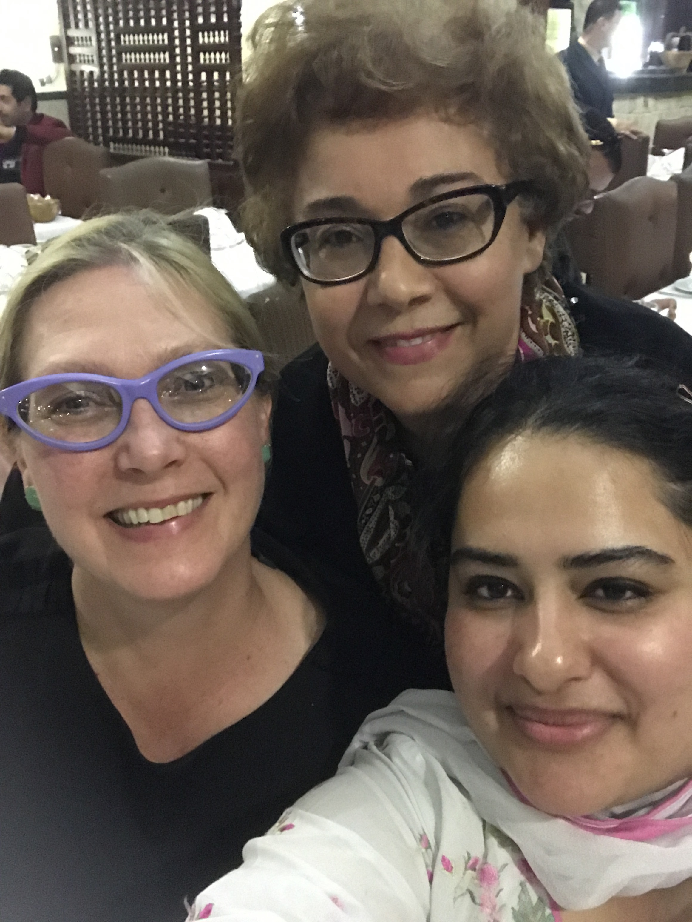 Ashley, Raja, and Zahra pose for a casual selfie at the final dinner with the team and participants.