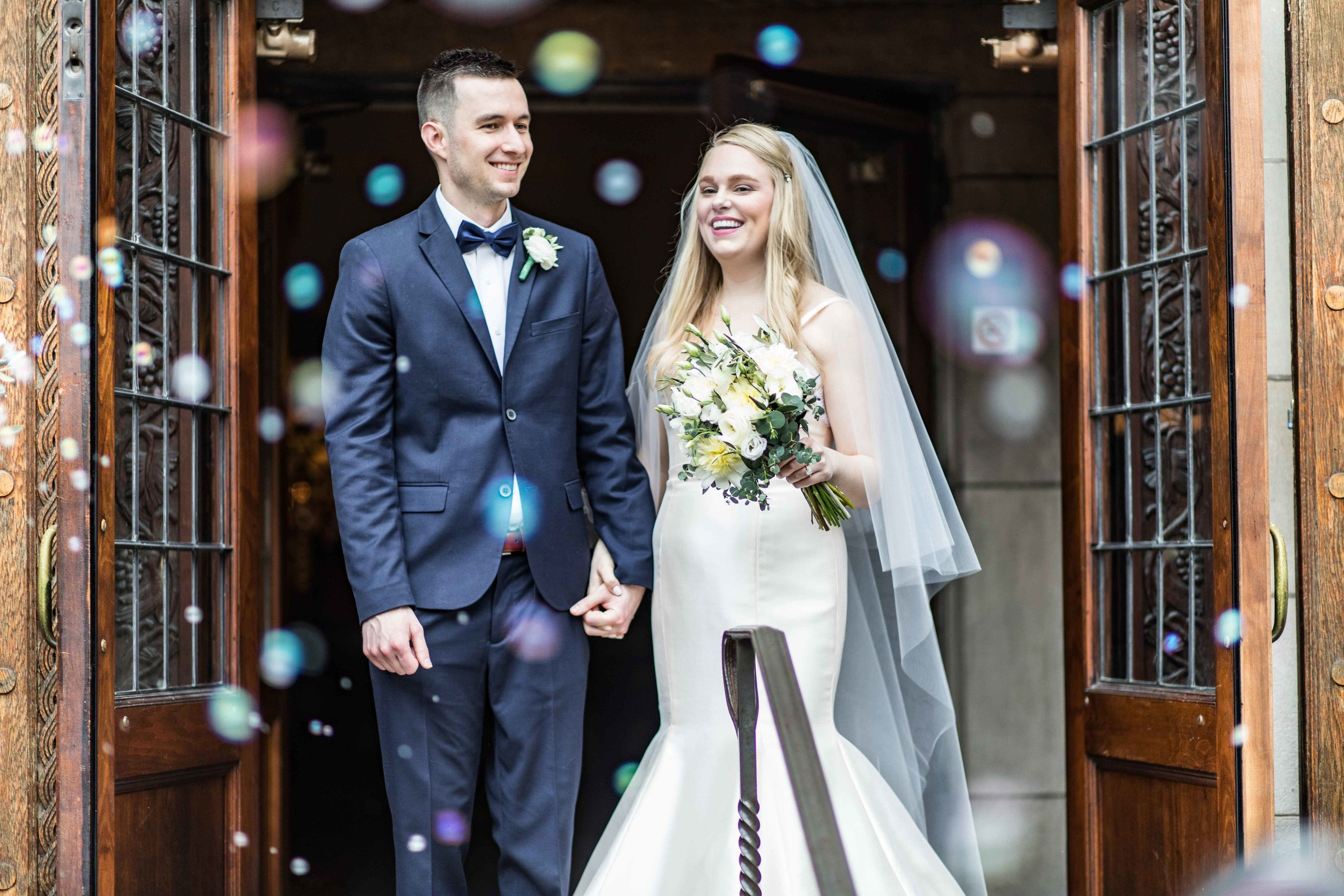 Bride and Groom bubble exit from the tall wood church doors