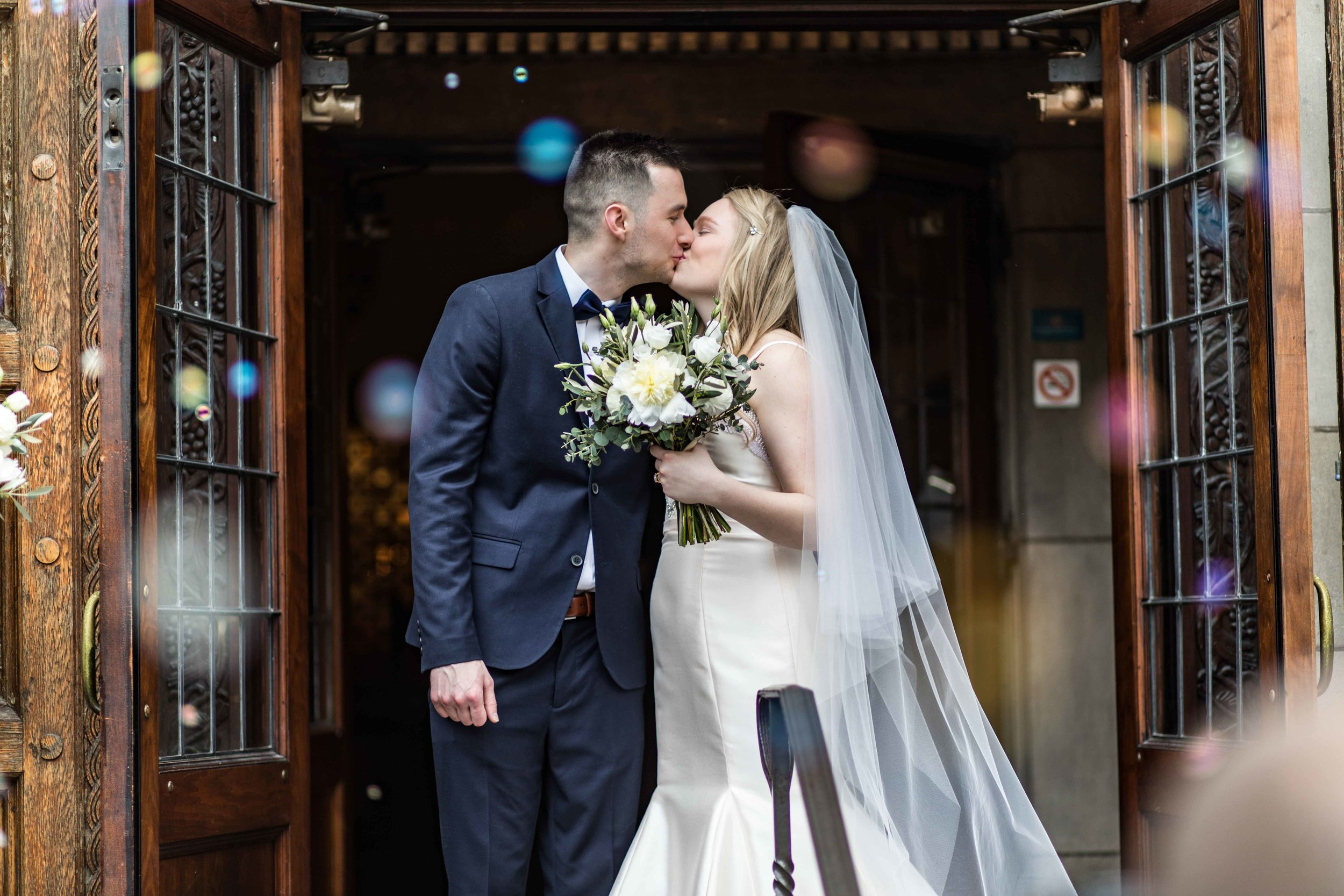 Bride and Groom kiss in a cloud of bubbles in front of church