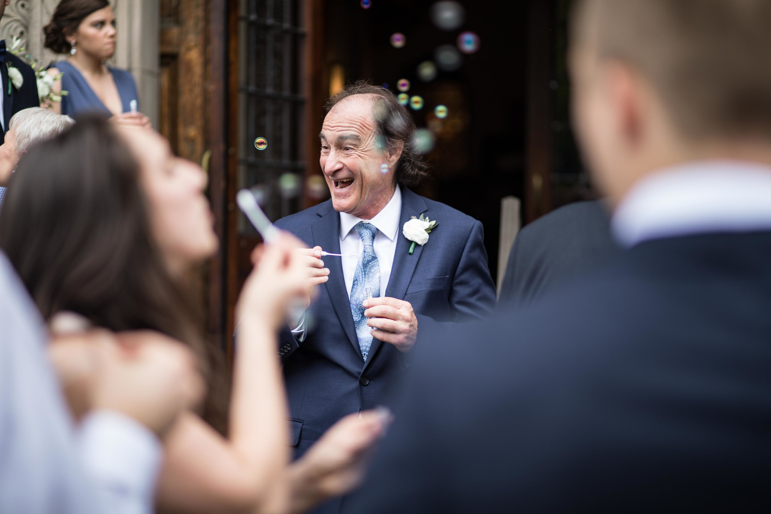 Father of the Groom blowing bubbles and laughing