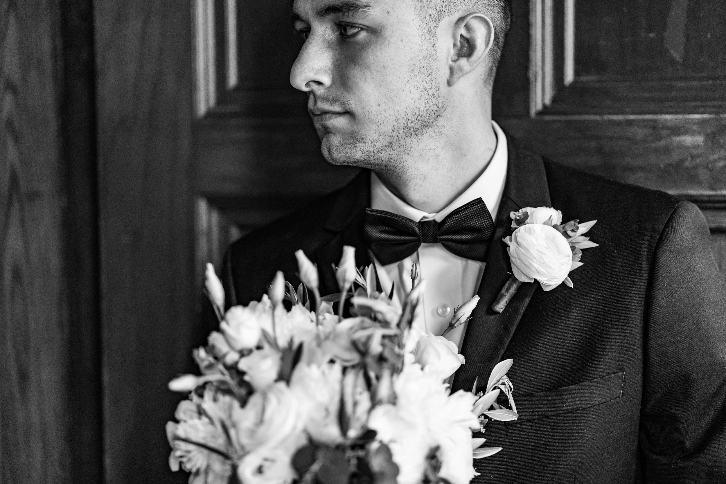 The Groom holding the brides bouquet against church door