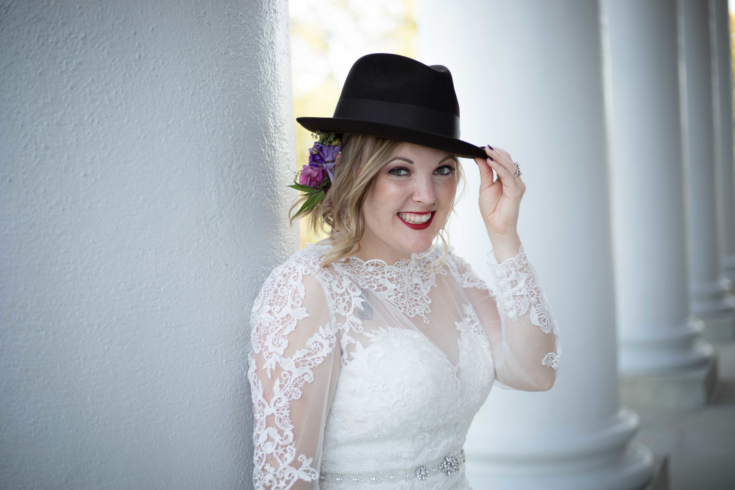 The bride sporting the grooms hat at heritage hall on western michigan university's campus