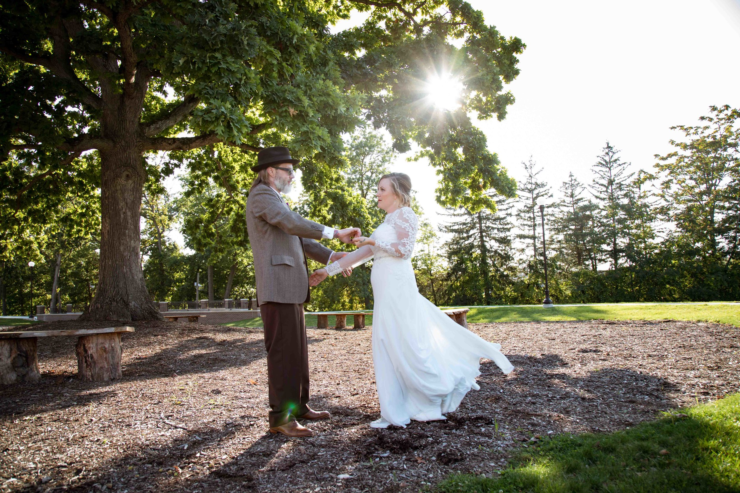 Bride and Groom dance in front of a setting sun