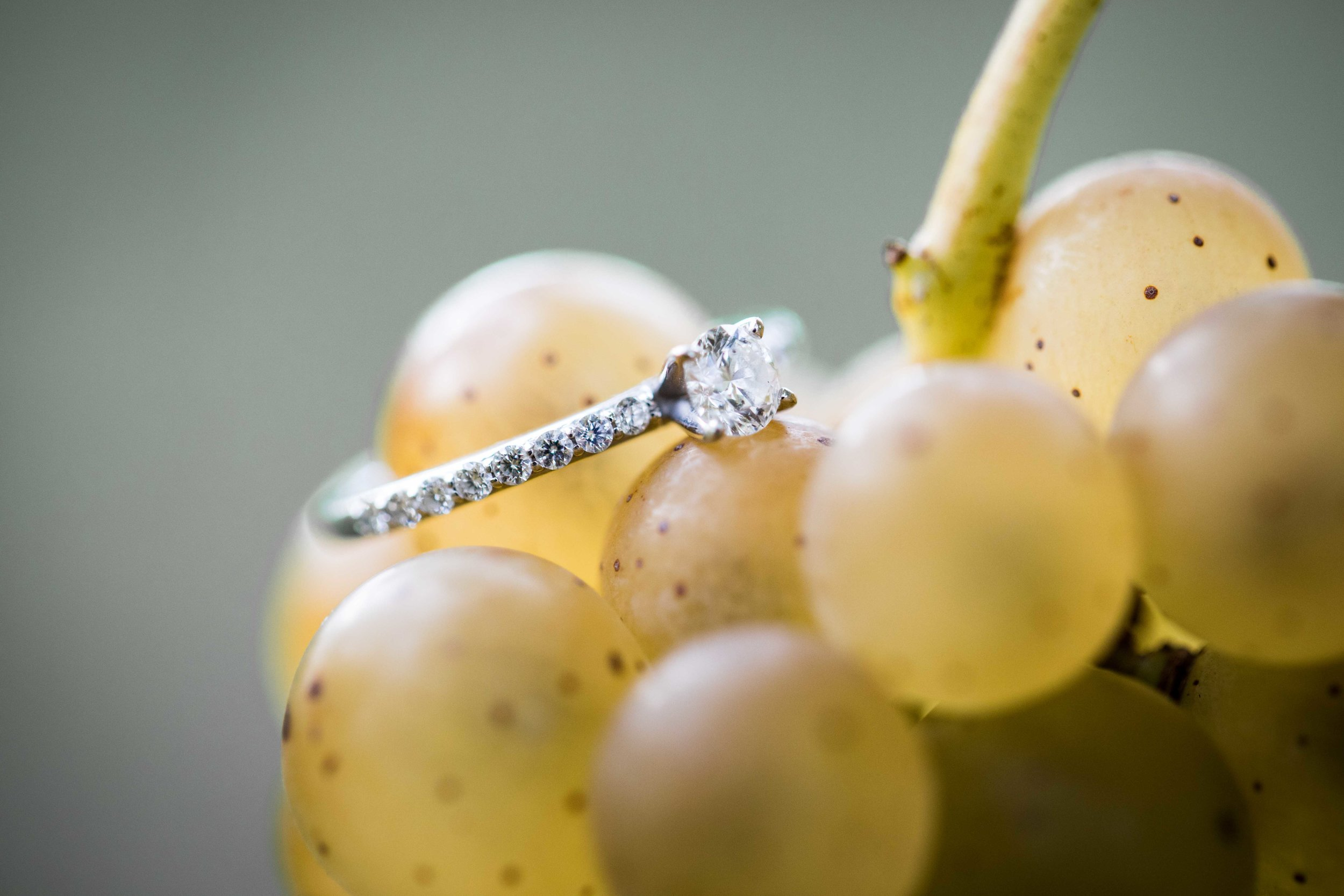 Engagement ring on grapes in the vineyard