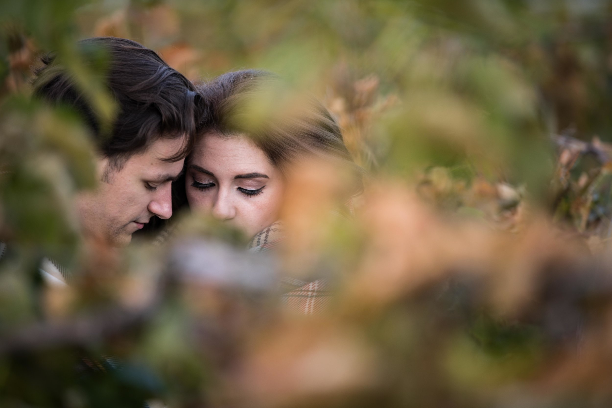 couple cuddling in the vineyard surrounded by grapevines
