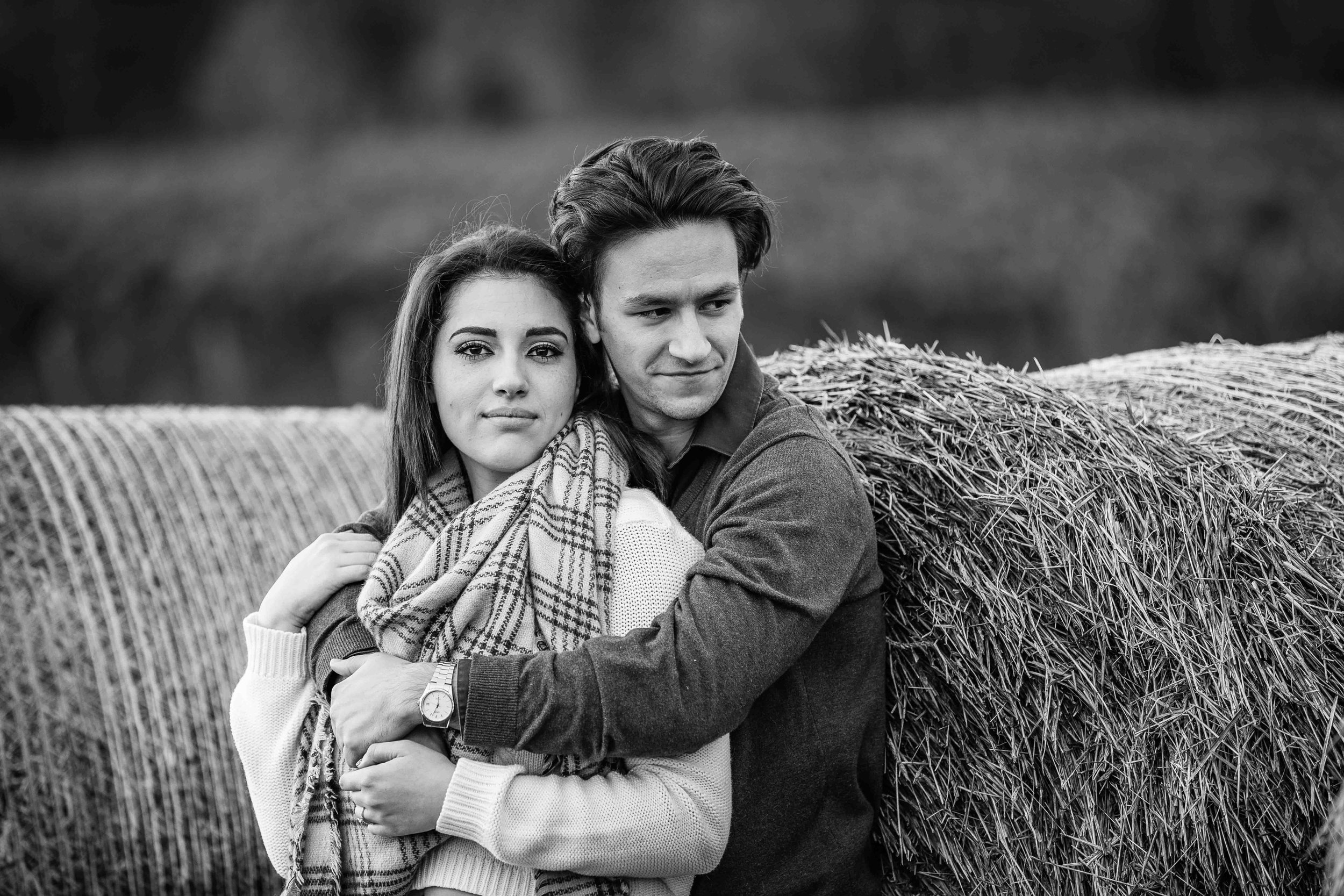 couple leaning on hay bale in field for engagement photos