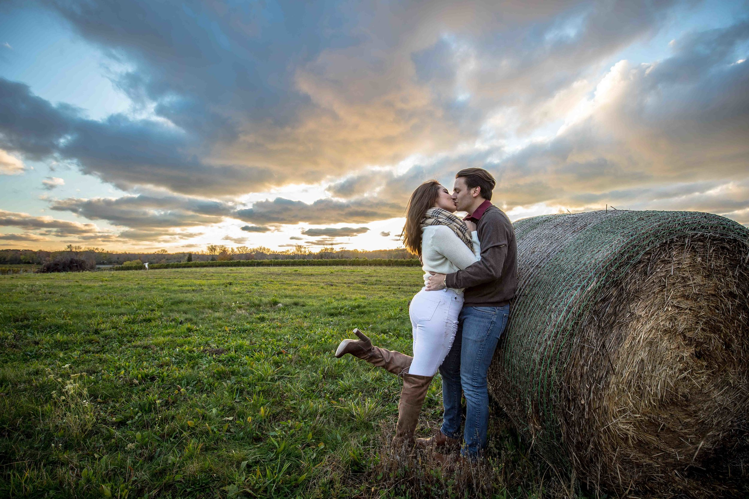 Leaning on hay bale with a leg kick kiss and a setting sun