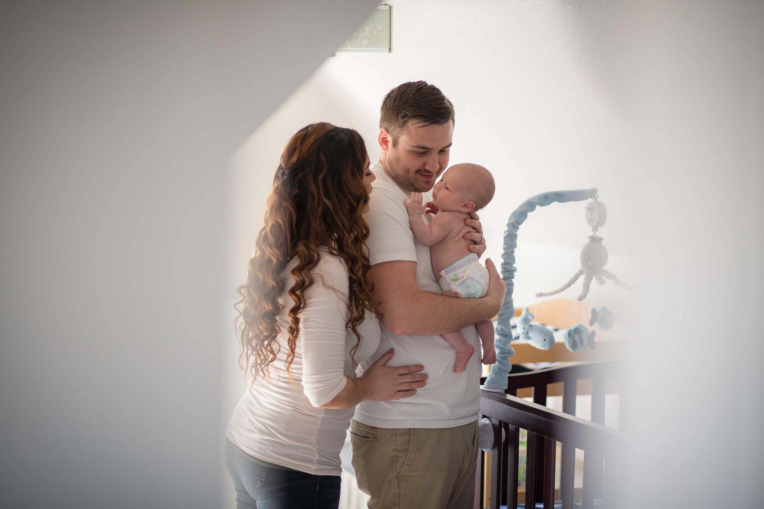 Father holds newborn son in nursery
