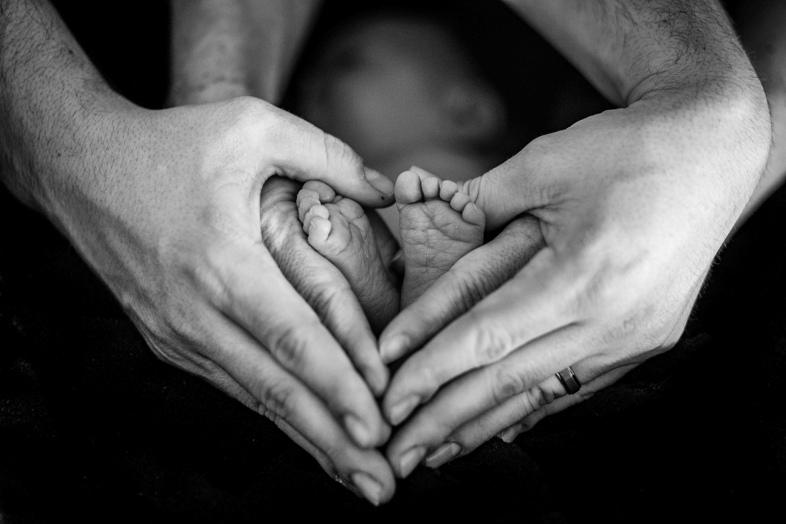mother and father make a heart shape with their hands and baby's feet