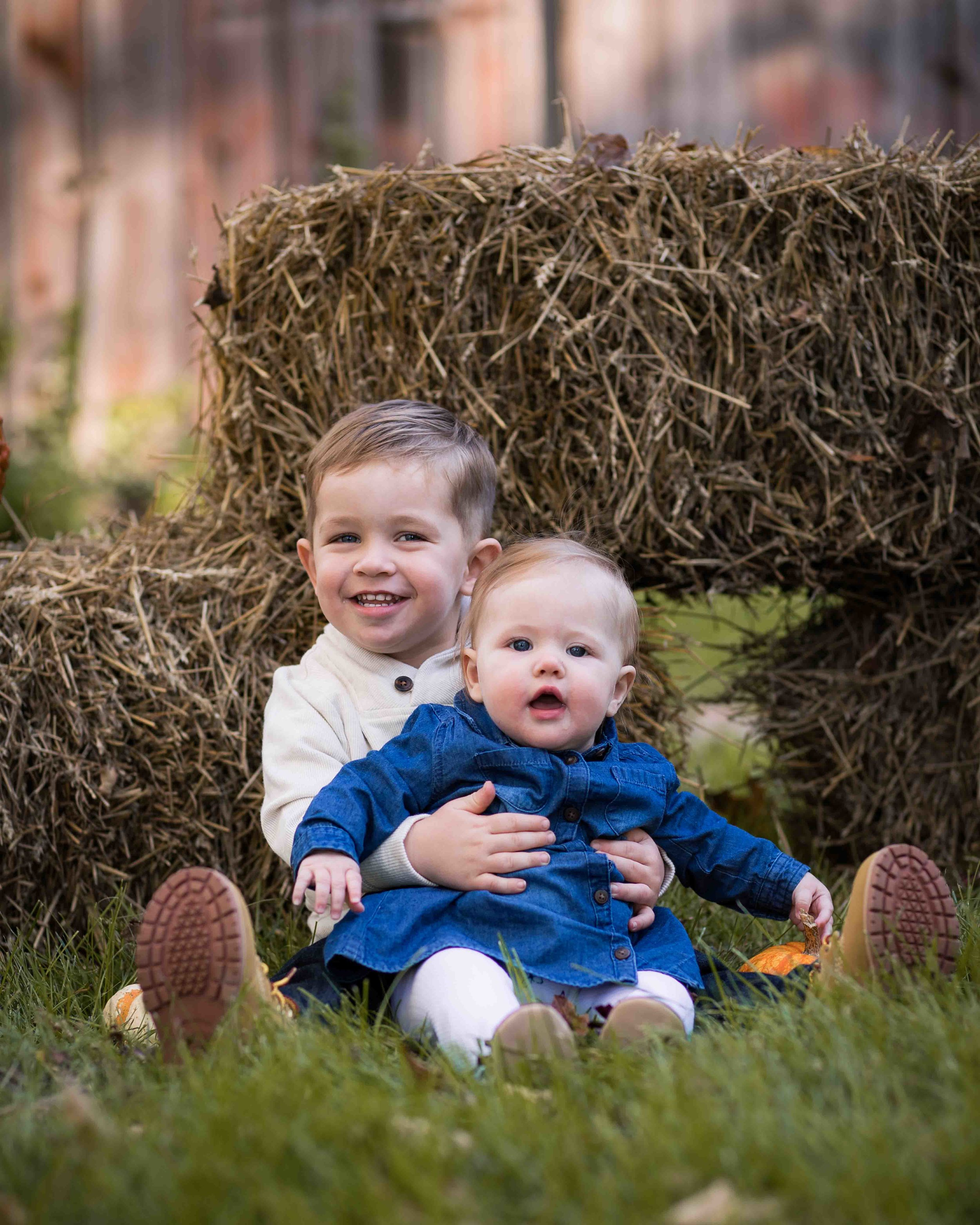 big brother holding his little sister in front of a hay bale at the Shiloh Farm barn in Richland, MI