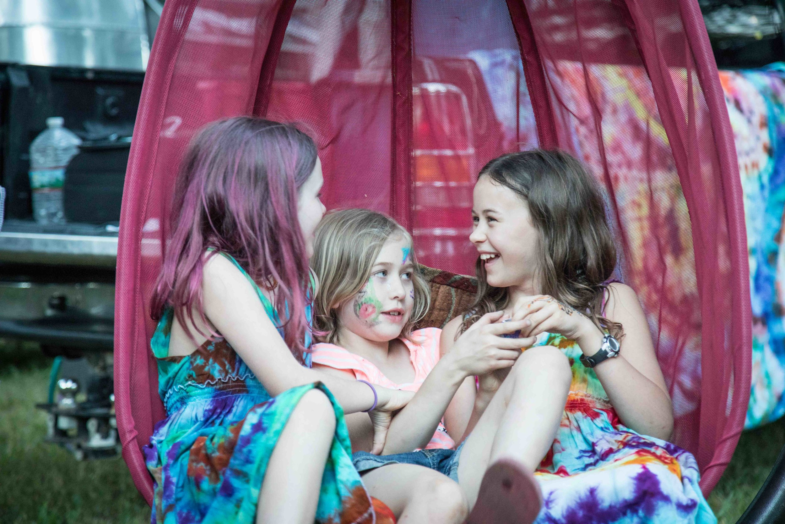 Three face painted children swinging in a hammock at the music festival