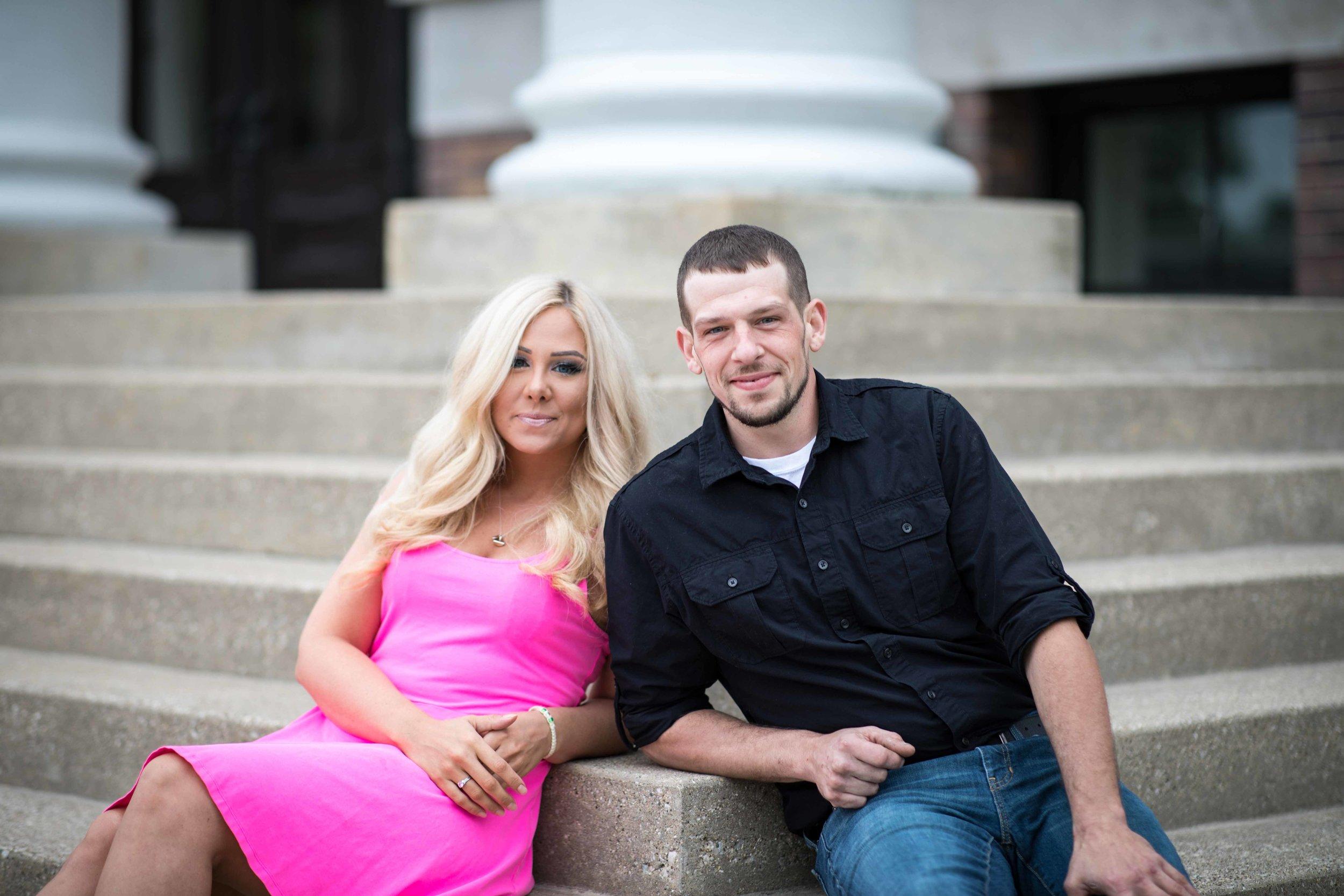 Engaged couple sitting on the steps of historic Heritage Hall in Kalamazoo