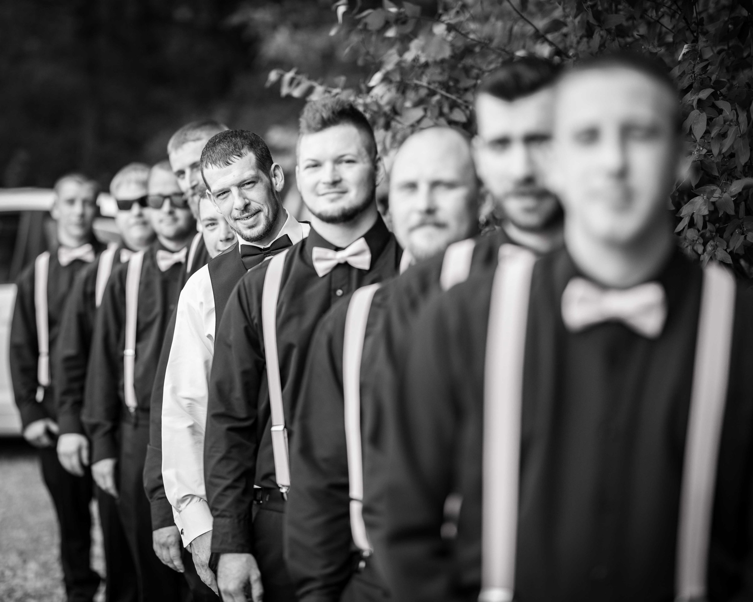 Grooms wedding party lines up for a black and white, focusing on the groom