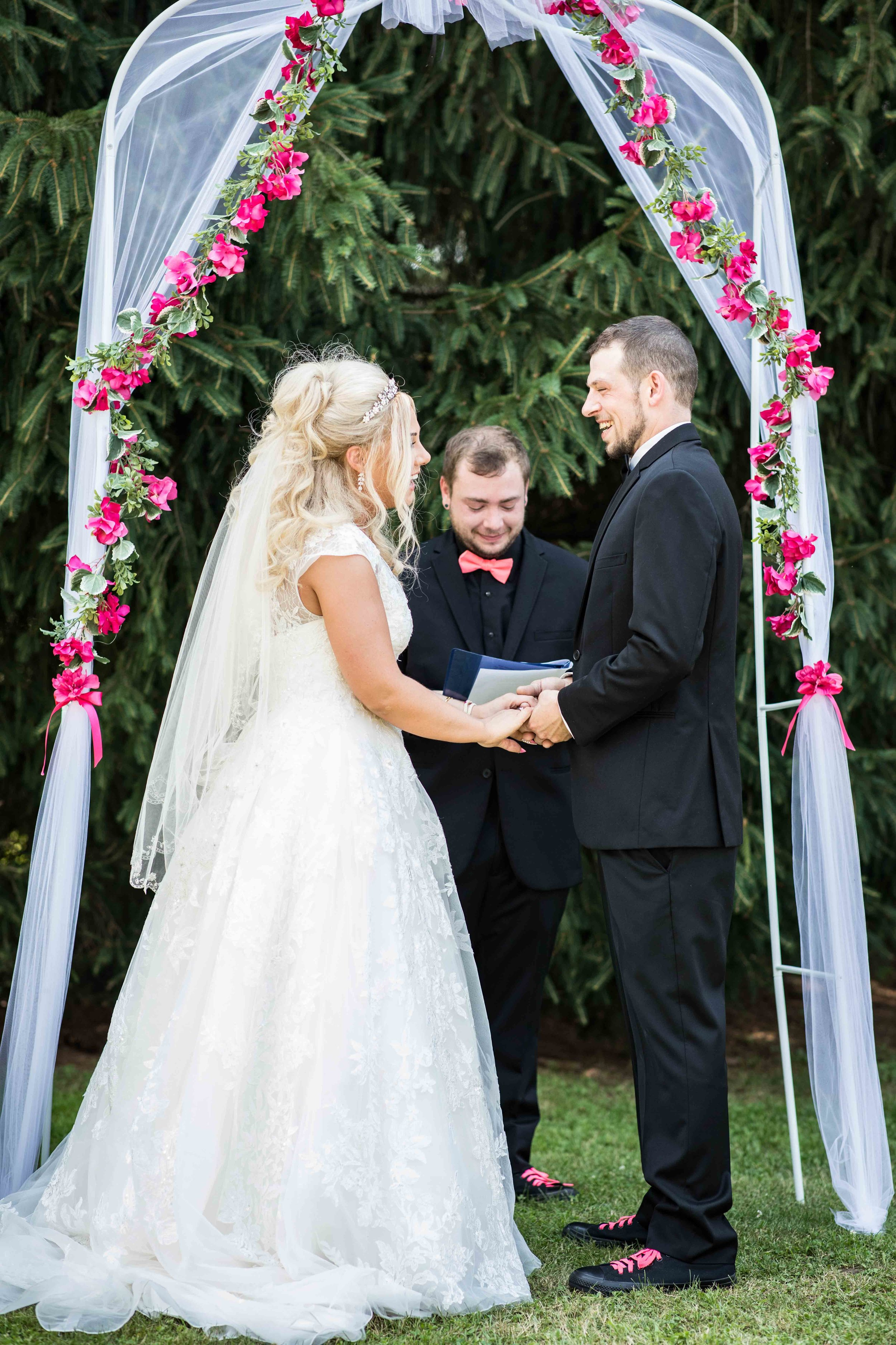 The couple holds hands as they stand together about to be wed