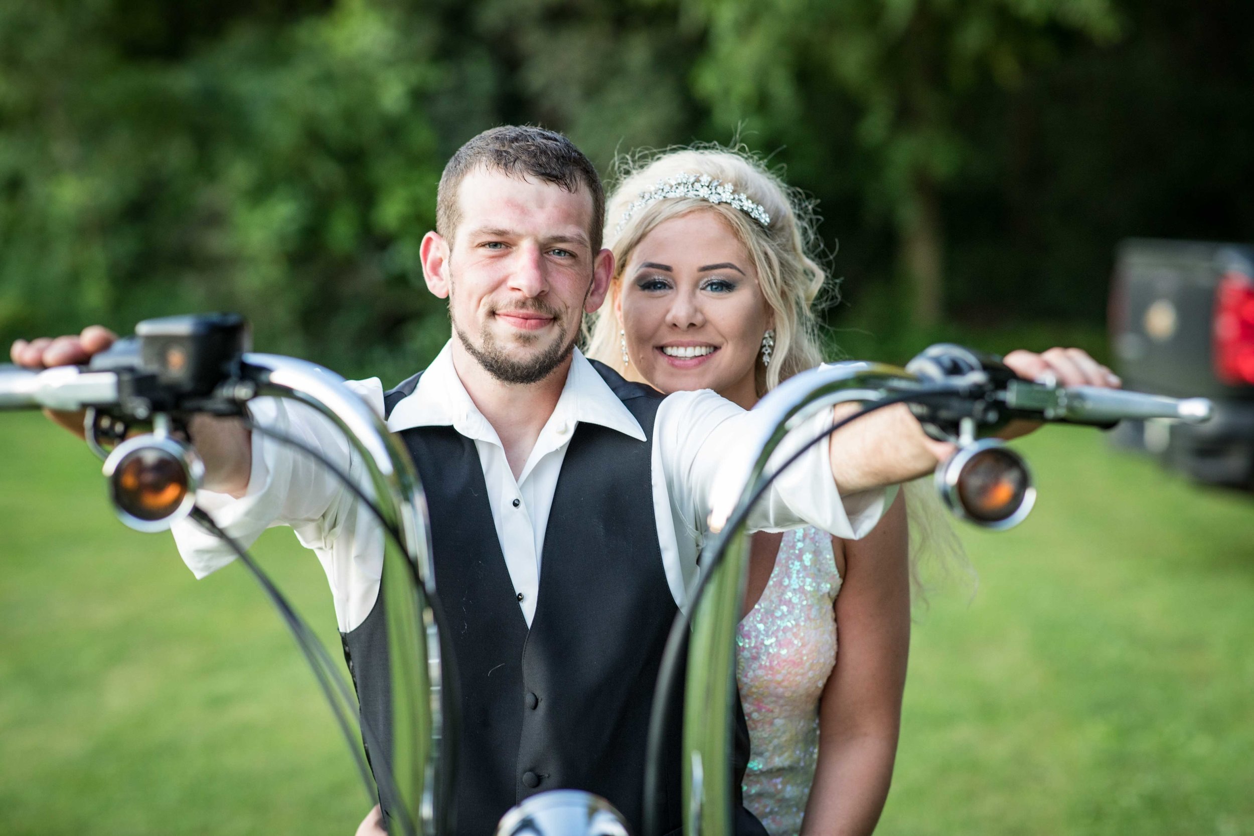 The Bride and Groom pose for a photo on the motorcycle before riding off together.