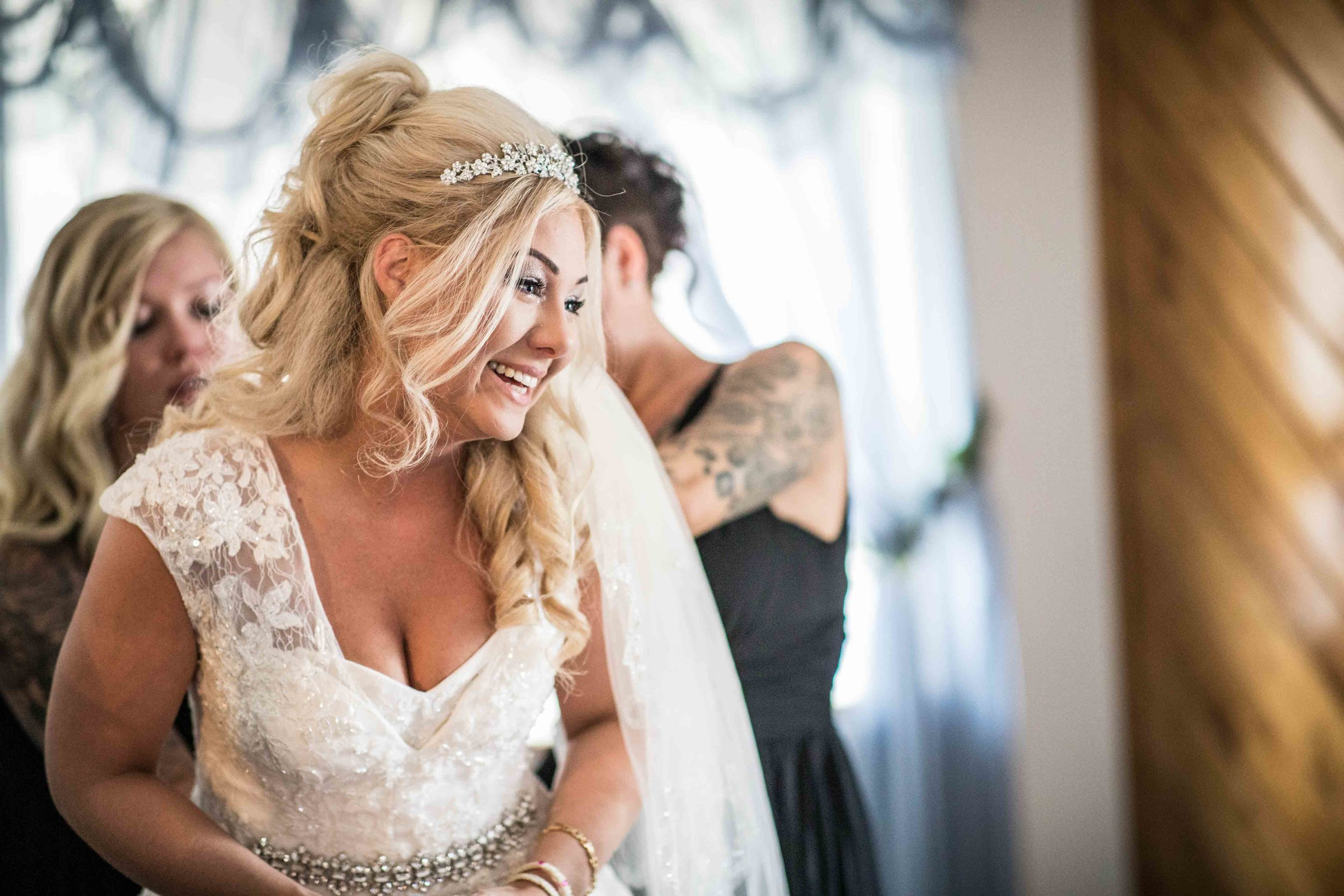 the bride laughs and cries all at the same time while her teams gets her ready